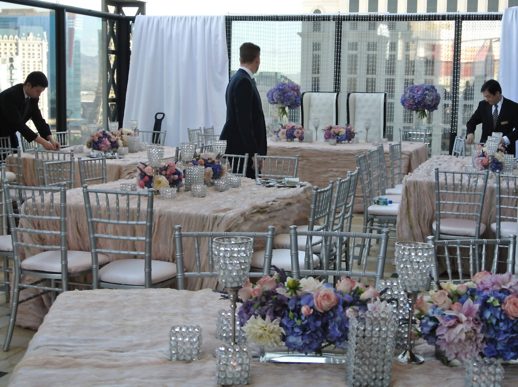 All hands were on deck to transform the balcony, removing the ceremony set up and bringing in custom tables, chairs, linens, and florals for the five course dinner reception.