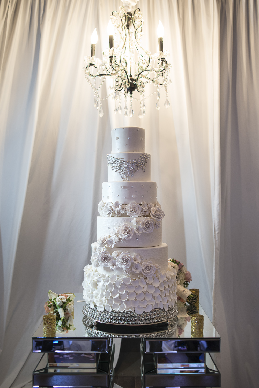 Jess and Juan's stunning six tiered cake is the first that I have ever designed myself.  The crystal pattern on the top echo the detail of her necklace, the roses call to mind her bouquet, and the petals below pick up the softness from the bottom of her dress.  The team at Mandarin Oriental took my rough sketch and turned out a masterpiece!  Photo by   AltF Photography  .