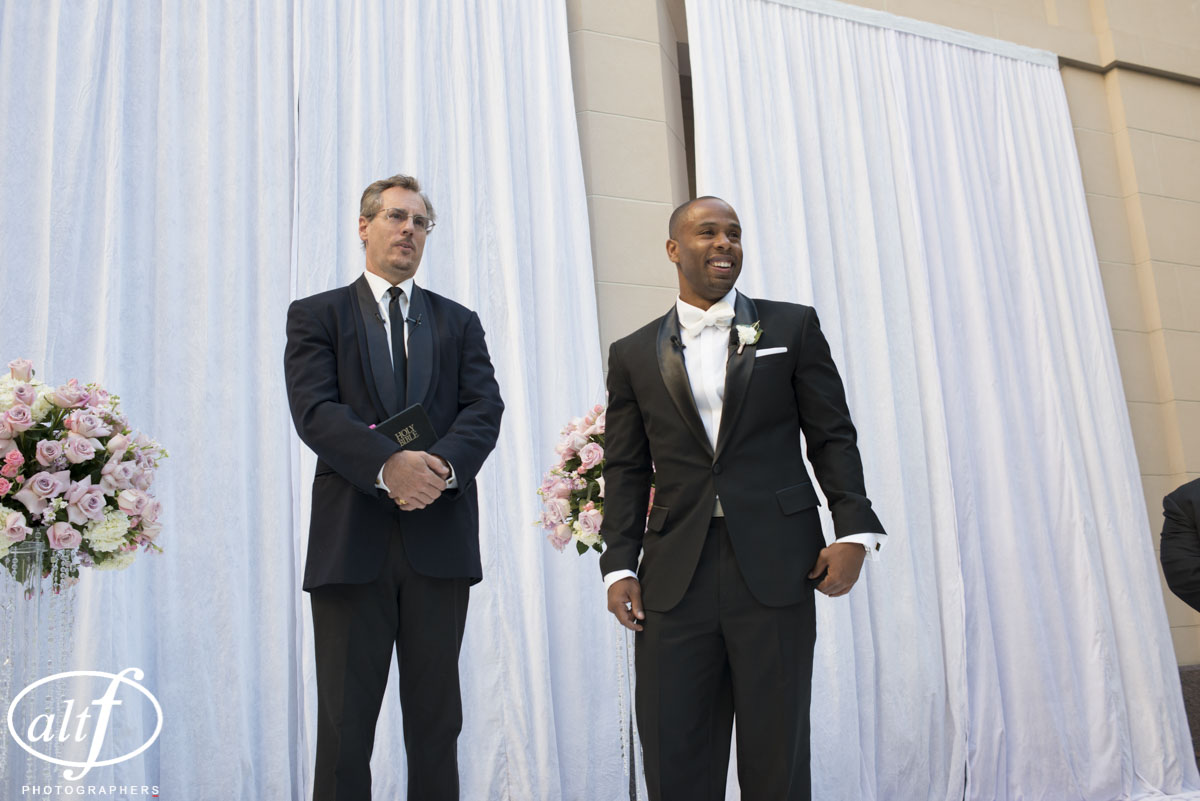The groom waiting at the aisle for his bride.