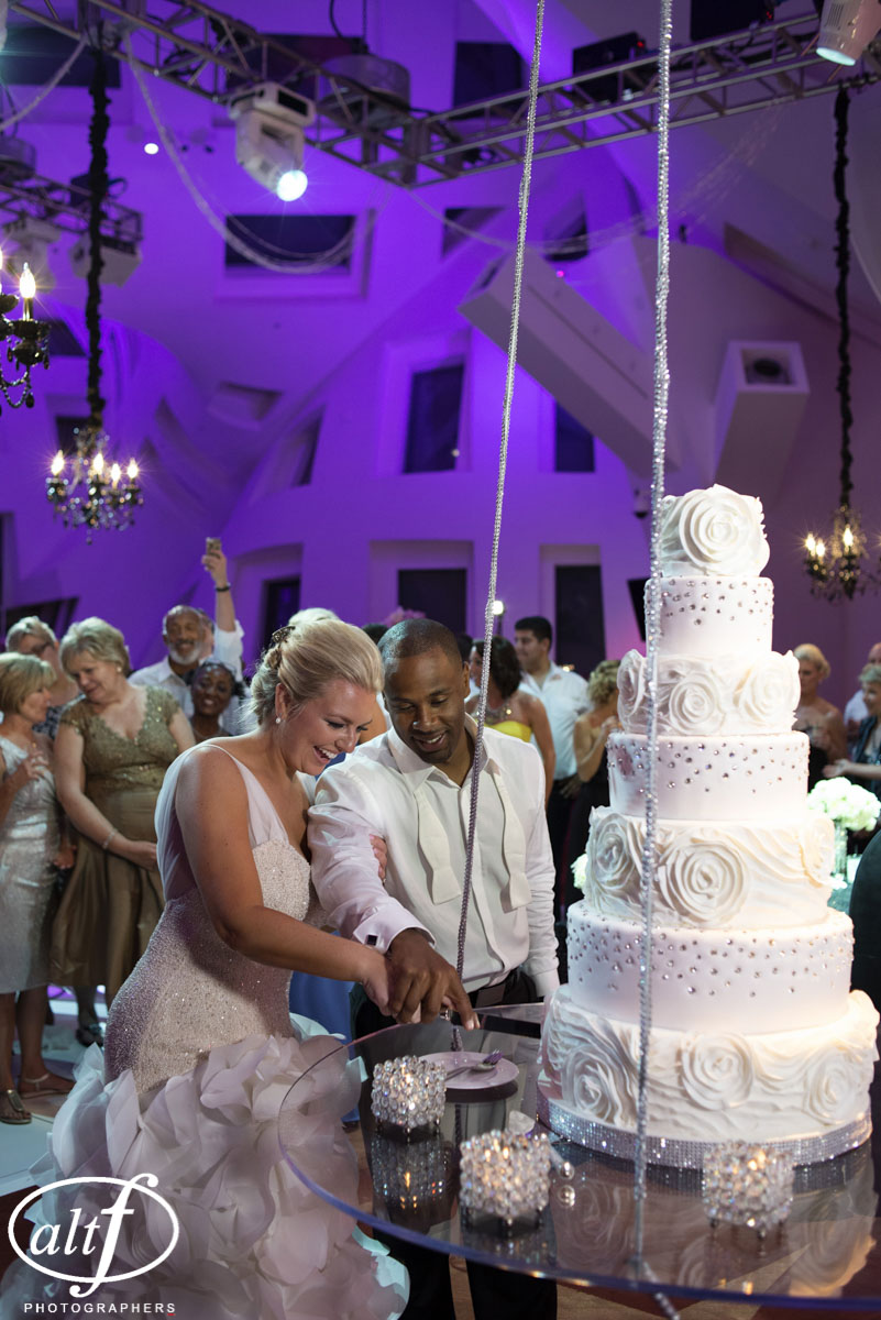 Bride and Groom Cutting the Cake. Wedding Cake by Peridot Sweets at Keep Memory Alive Center.