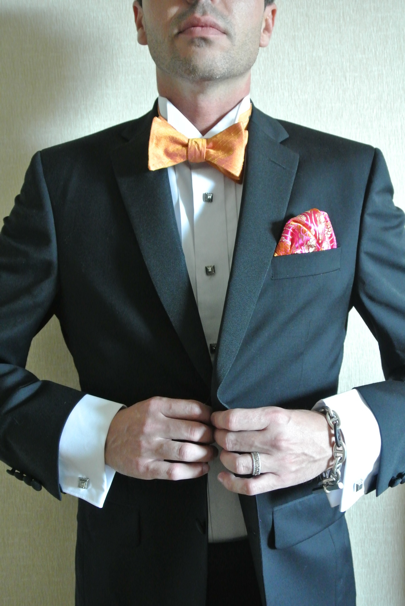 To marry his long time love, Marek accessorized his Vera Wang Black Tux with custom made orange bowtie, a pink and tangerine pocket square, and both cufflinks and button covers. His chocolate diamond engagement ring was firmly on his finger.   Las Vegas Wedding Planner Andrea Eppolito    Photo by Andrea Eppolito.