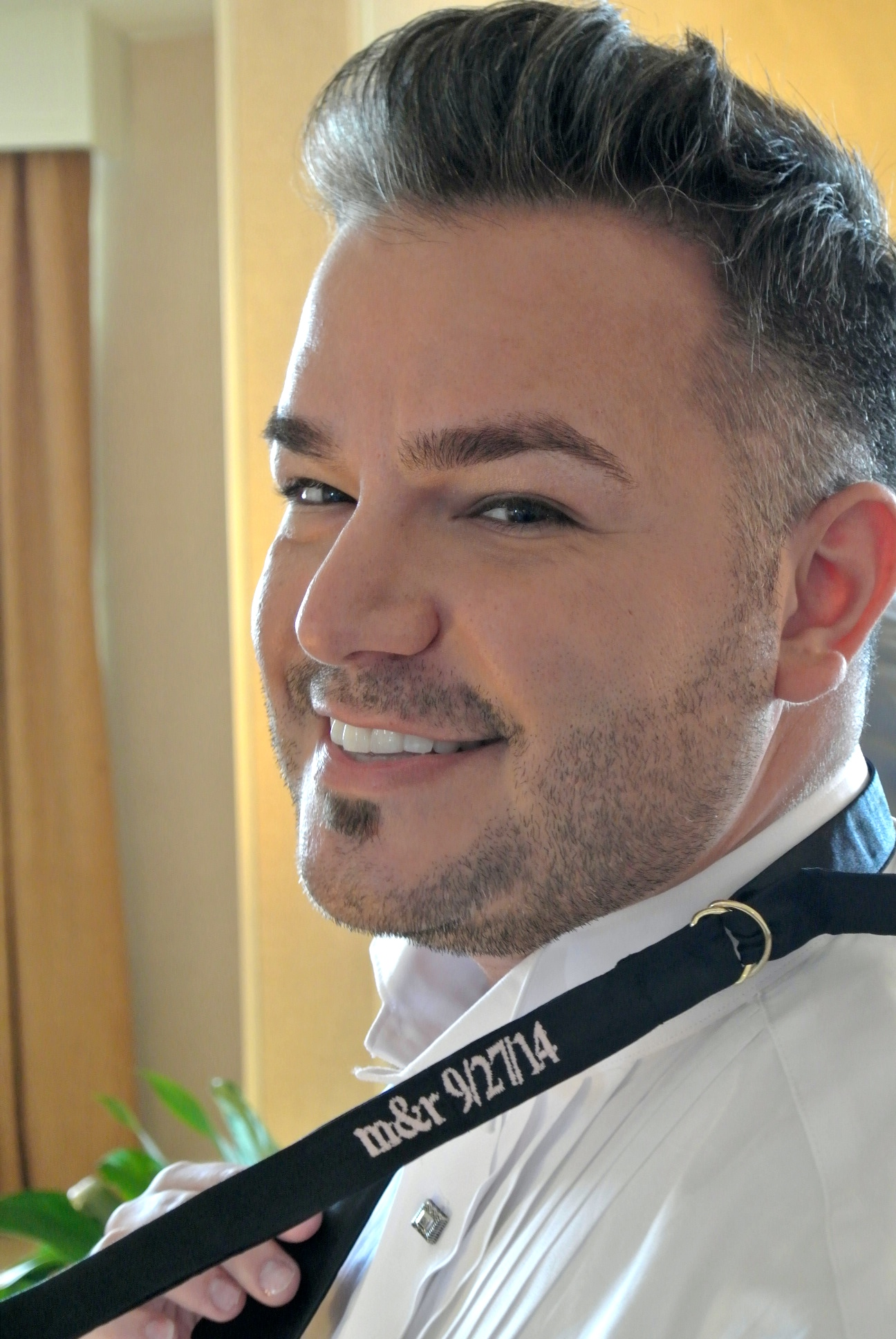 Known throughout Las Vegas for his irreverent style, Rocco opted to leave his embroidered bowtie undone, with the M&R logo and his wedding date proudly on display. September 2014.   Las Vegas Wedding Planner Andrea Eppolito    Photo by Andrea Eppolito.