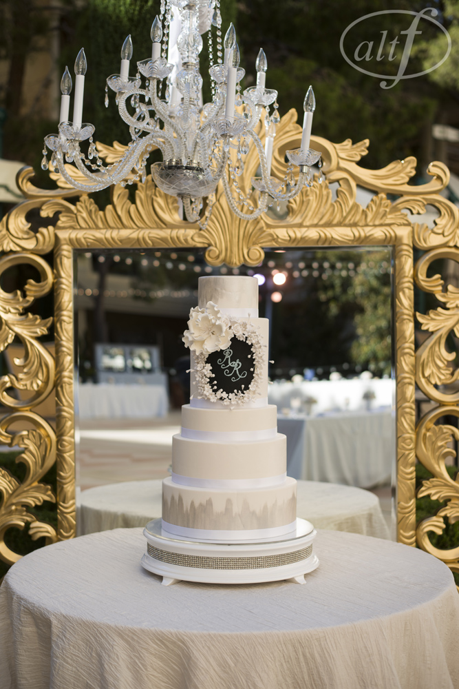 The Bellagio Pastry Chef created this five tiered confection, keeping it clean with shades of white and ivory.  The hand painted platinum on the top and bottom tiered added just the right amount of sparkle, and the couple's chalked monogram was surrounded by hand made sugar flowers and a large magnolia.  For extra glamour, we set the cake in front of a large golden mirror and hung a chandelier up above.  Photo by  w w.