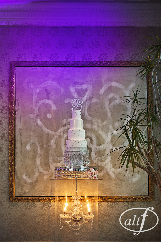 For Megan and Alan, we literally turned the trends upside down, placing the cake on top of the chandelier, and not below it.  The dramatic display held the four tiered wedding cake created by  Peridot Sweets  up nice and high for the couple's wedding in the villas of Caesars Palace.  Photo by  Alt F Photography .