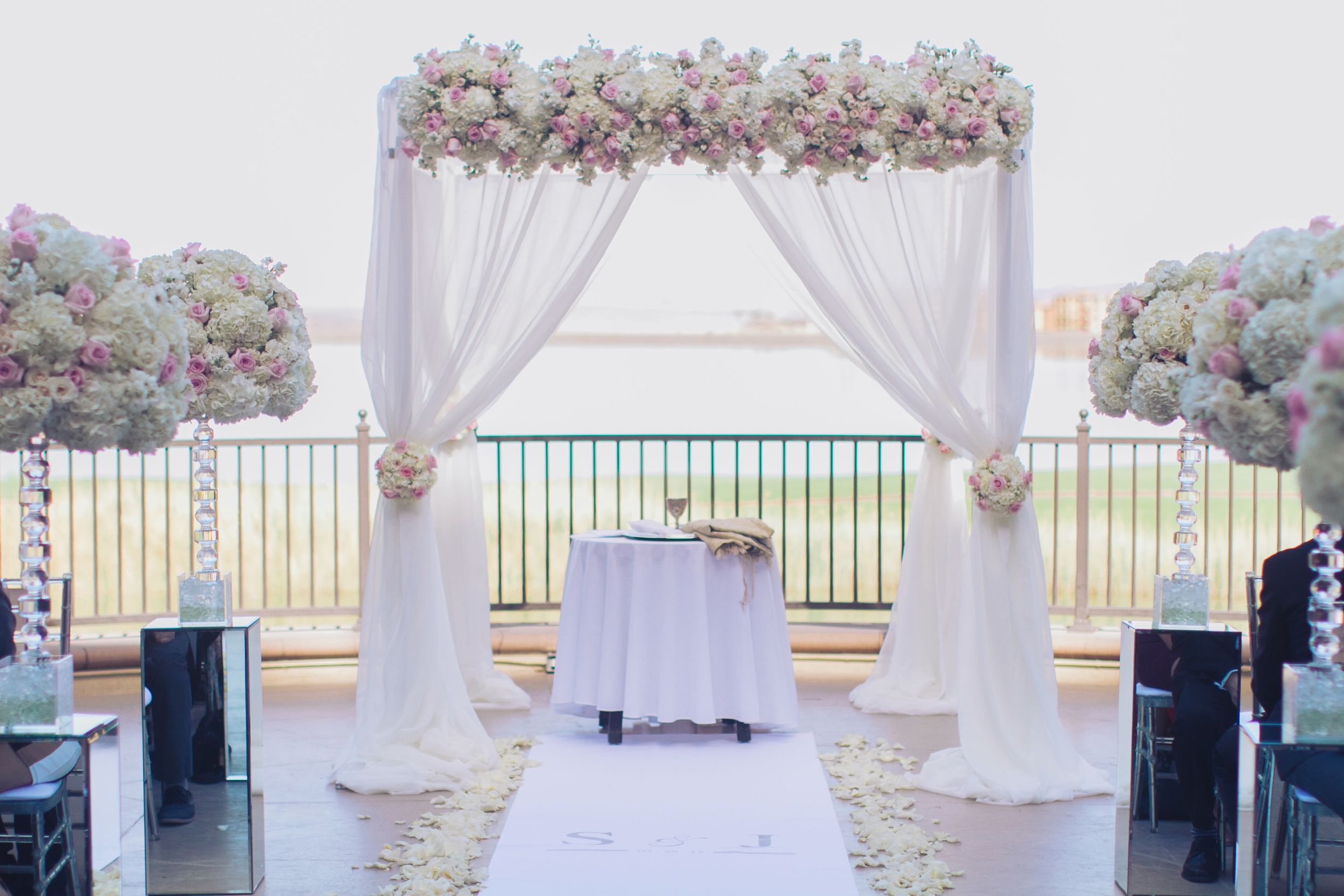 For the lakeside ceremony we dressed a chuppah in flowing ivory fabric topped with ivory and pale pink roses. Matching topiaries lined the aisle.    Las Vegas Wedding Planner Andrea Eppolito   Wedding at Lake Las Vegas   White and Blu  sh and Grey Wedding   Luxury Wedding Las Vegas