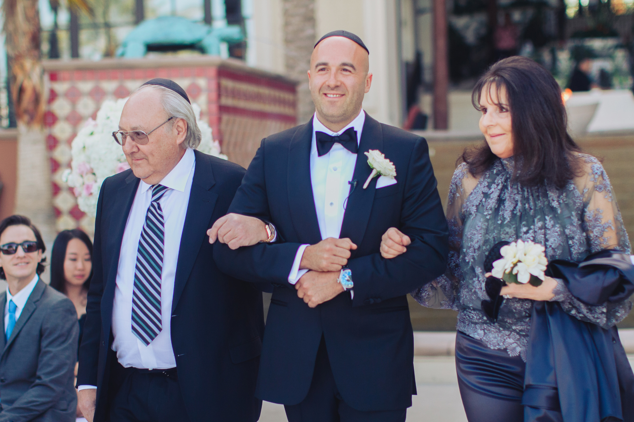 The groom was escorted down the aisle by both his parents.    Las Vegas Wedding Planner Andrea Eppolito   Wedding at Lake Las Vegas   White and Blu  sh and Grey Wedding   Luxury Wedding Las Vegas