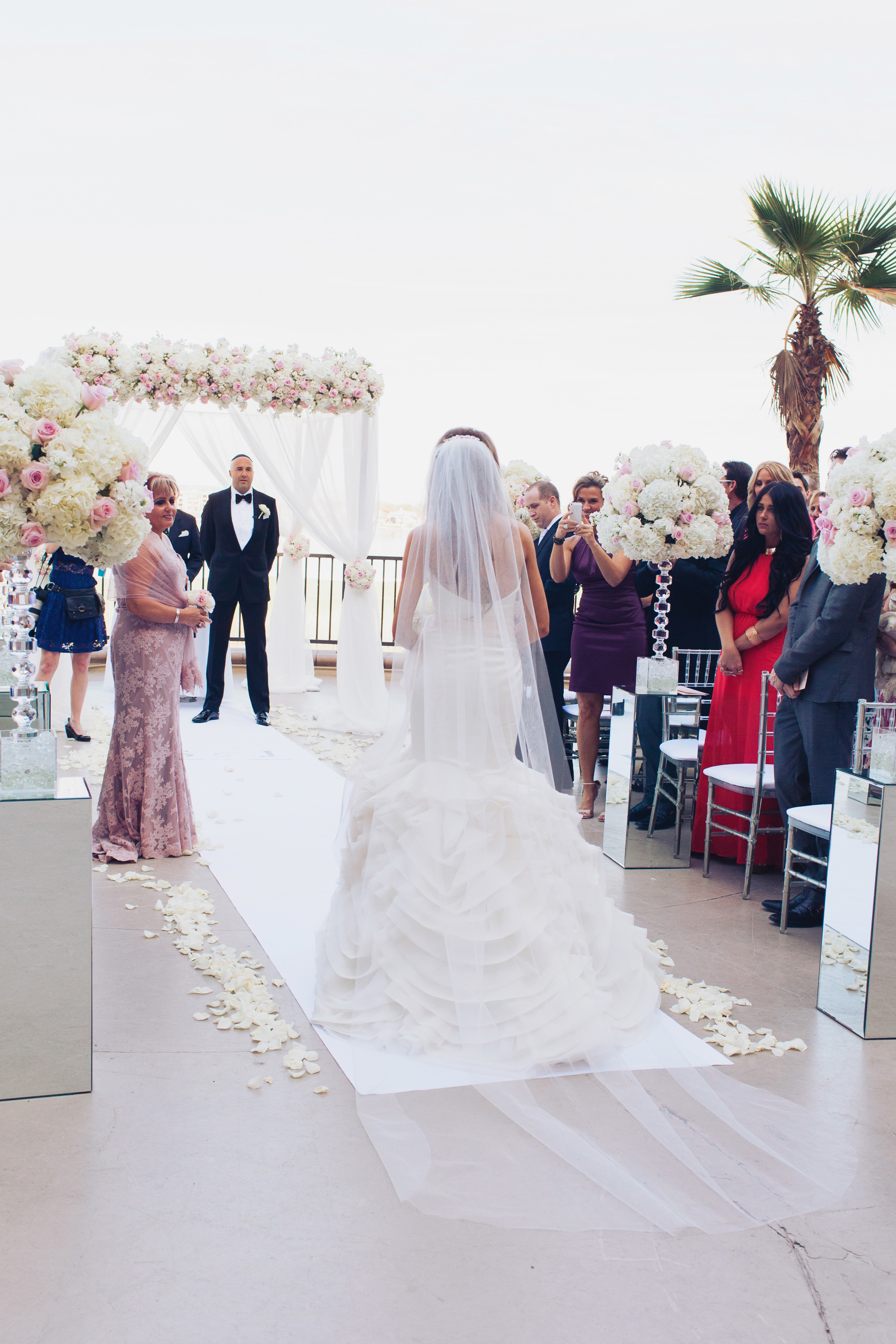 The bride walked half way down the aisle on her own before meeting her mother, who gave her away at the end.    Las Vegas Wedding Planner Andrea Eppolito   Wedding at Lake Las Vegas   White and Blu  sh and Grey Wedding   Luxury Wedding Las Vegas
