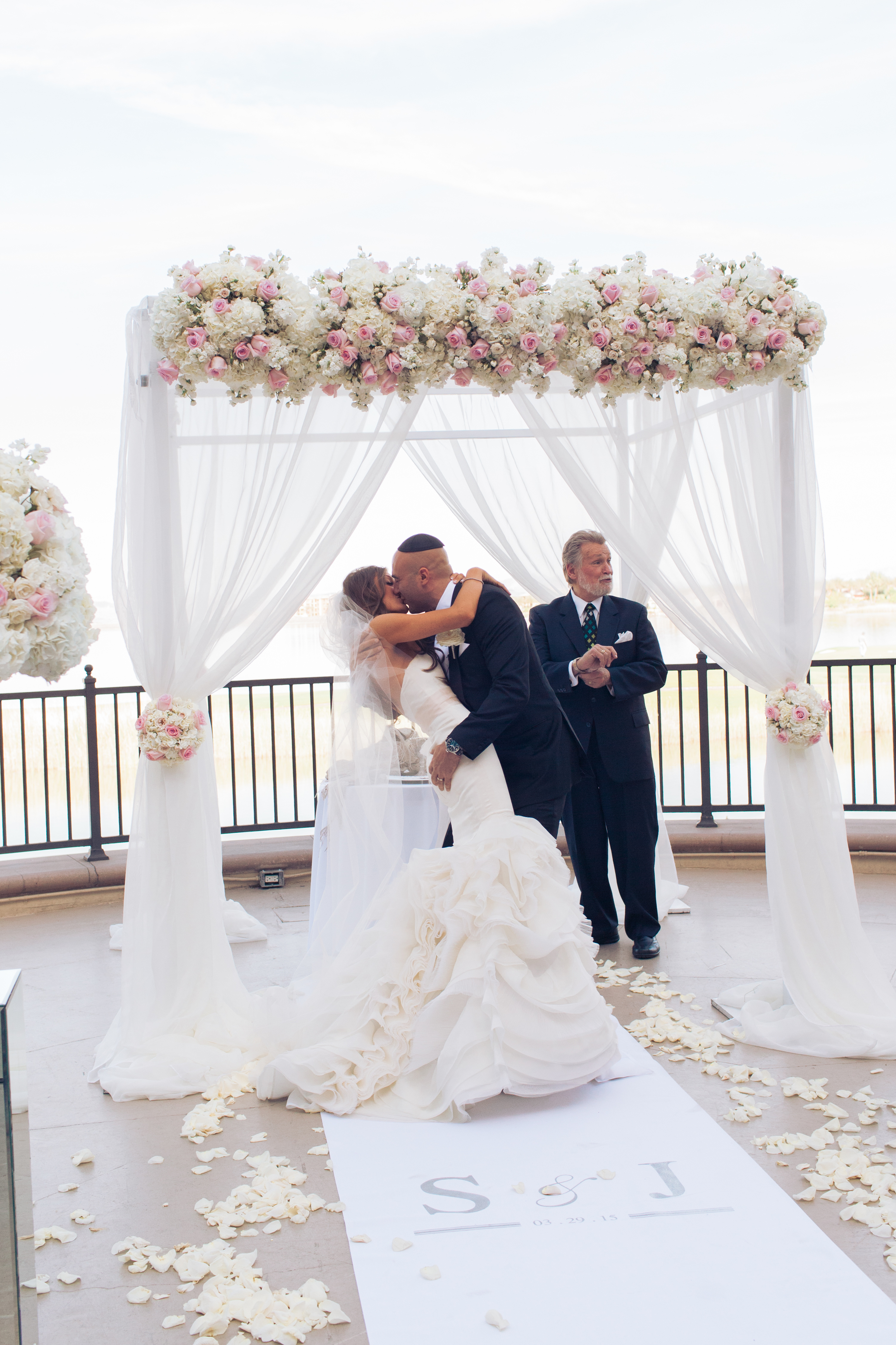 The couple's dramatic first kiss had the groom dipping the bride in front of their guests and Rabbi Mel Hecht.    Las Vegas Wedding Planner Andrea Eppolito   Wedding at Lake Las Vegas   White and Blu  sh and Grey Wedding   Luxury Wedding Las Vegas