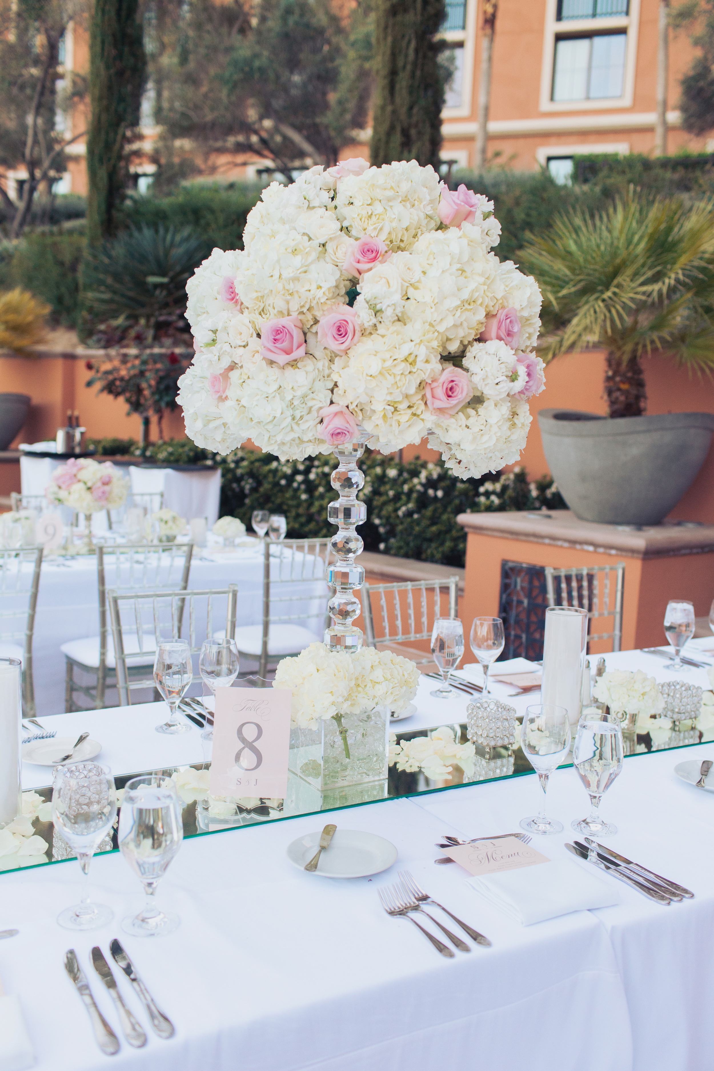 Cut crystal topiary bases upped the glamorous feel and held high centerpieces of white and ivory hydrangea dotted with baby pink and blush roses. Cresol candle holders, rose petals, and votives gave a soft, romantic feel.  Las Vegas Wedding Planner Andrea Eppolito   Wedding at Lake Las Vegas   White and Blu  sh and Grey Wedding