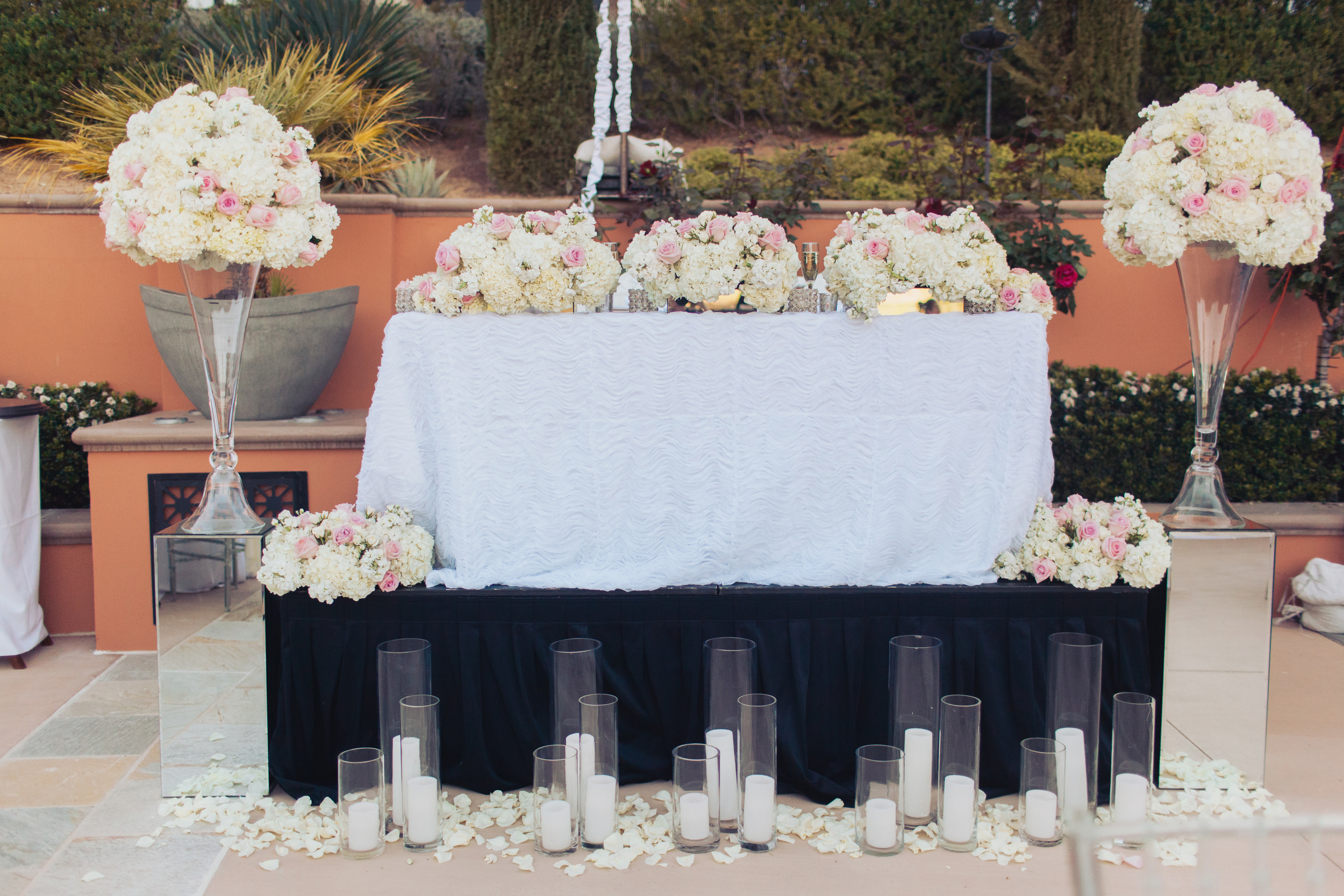 The bride and groom sat at an elevated sweetheart table dressed in a textured white linen, surrounded by lush, full floral arrangements and candles.    Las Vegas Wedding Planner Andrea Eppolito   Wedding at Lake Las Vegas   White and Blu  sh and Grey Wedding   Luxury Wedding Las Vegas