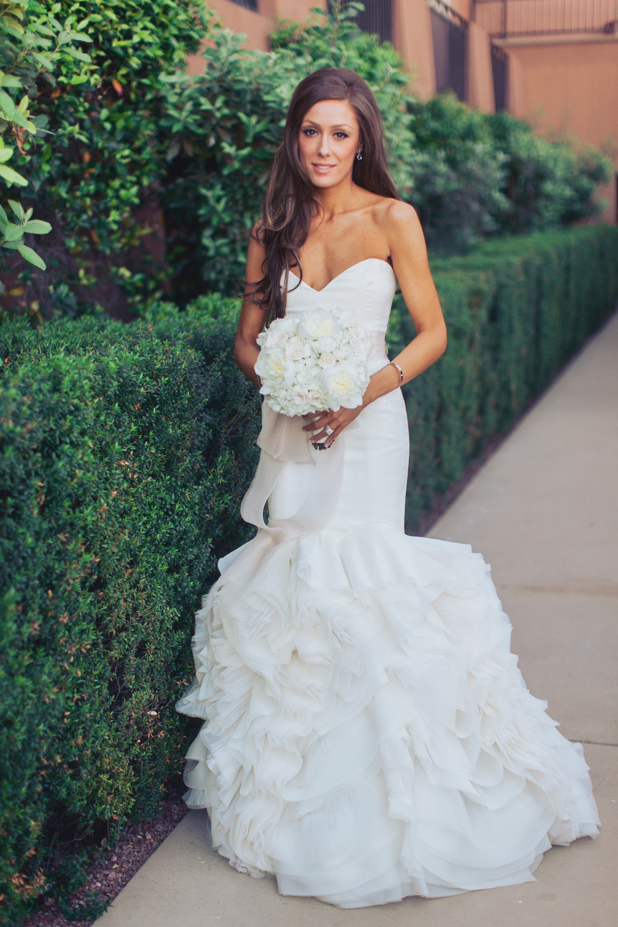 The bride wore an ivory gown by Rivini accented with a blush bow. her Cartier LOVE bangle was a gorgeous compliment to her Tiffany & Co engagement ring and wedding band.    Las Vegas Wedding Planner Andrea Eppolito   Wedding at Lake Las Vegas   White and Blu  sh and Grey Wedding   Luxury Wedding Las Vegas