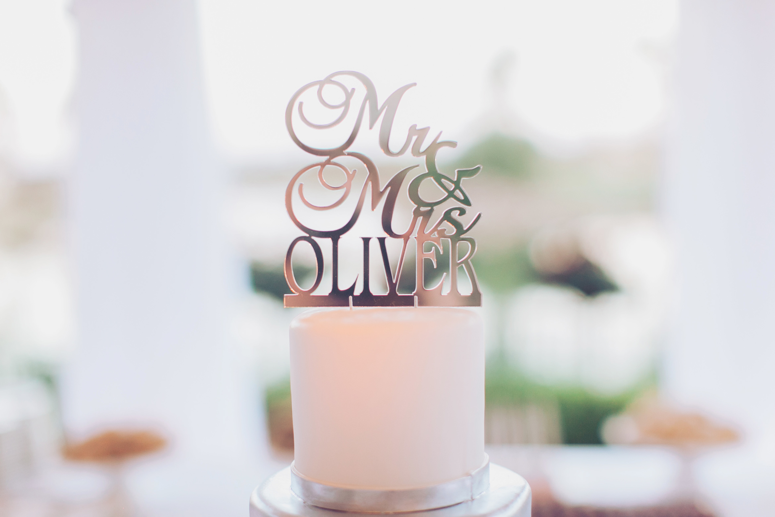 The top of the wedding cake featured a Mr. & Mrs Oliver cake topper.  Stephanie Di Lallo married  Justin Oliver at a water front  wedding at The Westin Lake Las Vegas.     Las Vegas Wedding Planner Andrea Eppolito   Wedding at Lake Las Vegas   White and Blu  sh and Grey Wedding   Luxury Wedding Las Vegas