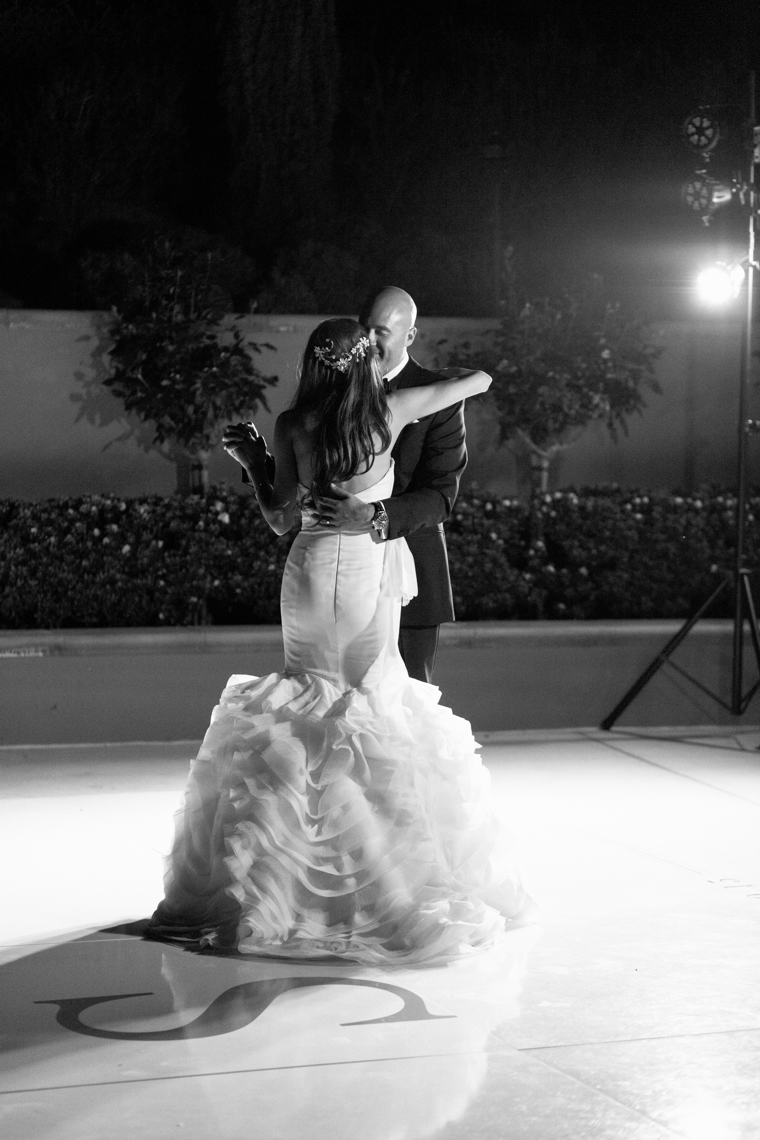 The bride and groom shared their first dance on a monogrammed dance floor.  Stephanie Di Lallo married  Justin Oliver at a water front  wedding at The Westin Lake Las Vegas.     Las Vegas Wedding Planner Andrea Eppolito   Wedding at Lake Las Vegas   White and Blu  sh and Grey Wedding   Luxury Wedding Las Vegas