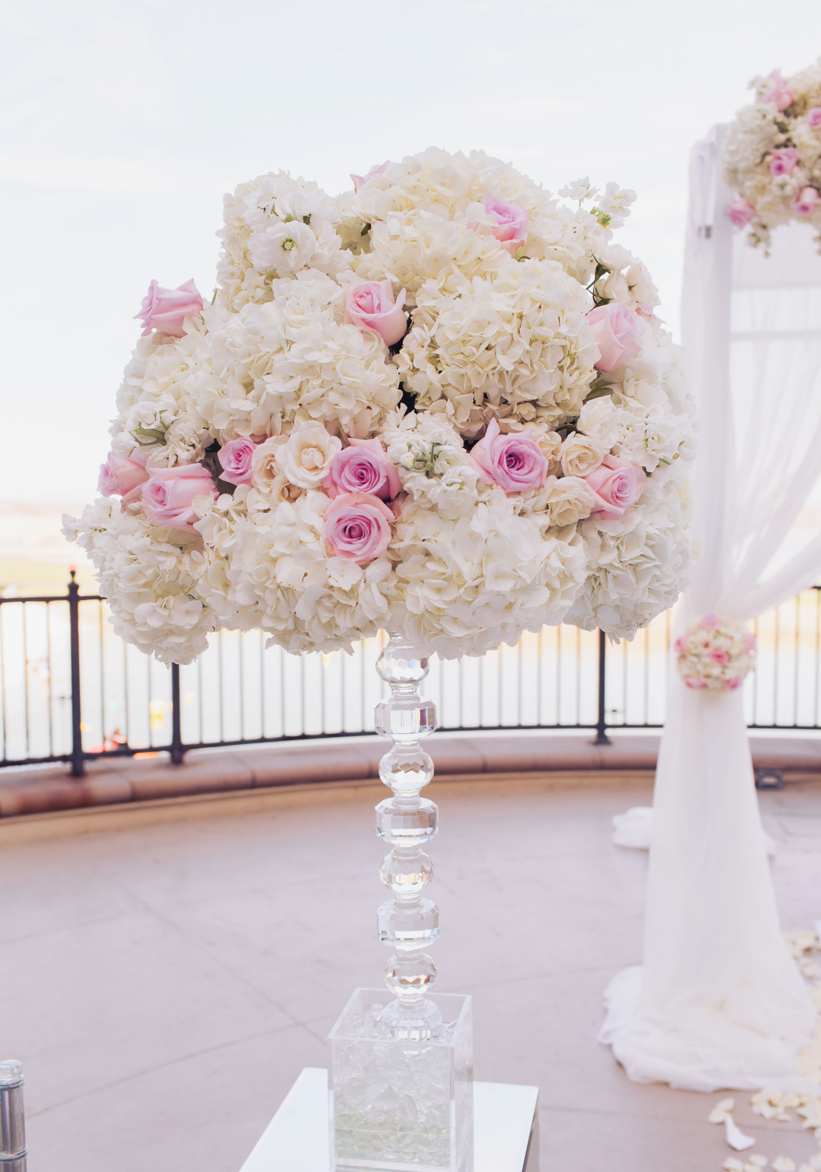 Pew markers were crafted of large, lush floral pieces made of hydrangea and roses, set on top of crystal bases.  For the lakeside ceremony we dressed a chuppah in flowing ivory fabric topped with ivory and pale pink roses. Matching topiaries lined the aisle.     Las Vegas Wedding Planner Andrea Eppolito   Wedding at Lake Las Vegas   White and Blu  sh and Grey Wedding   Luxury Wedding Las Vegas