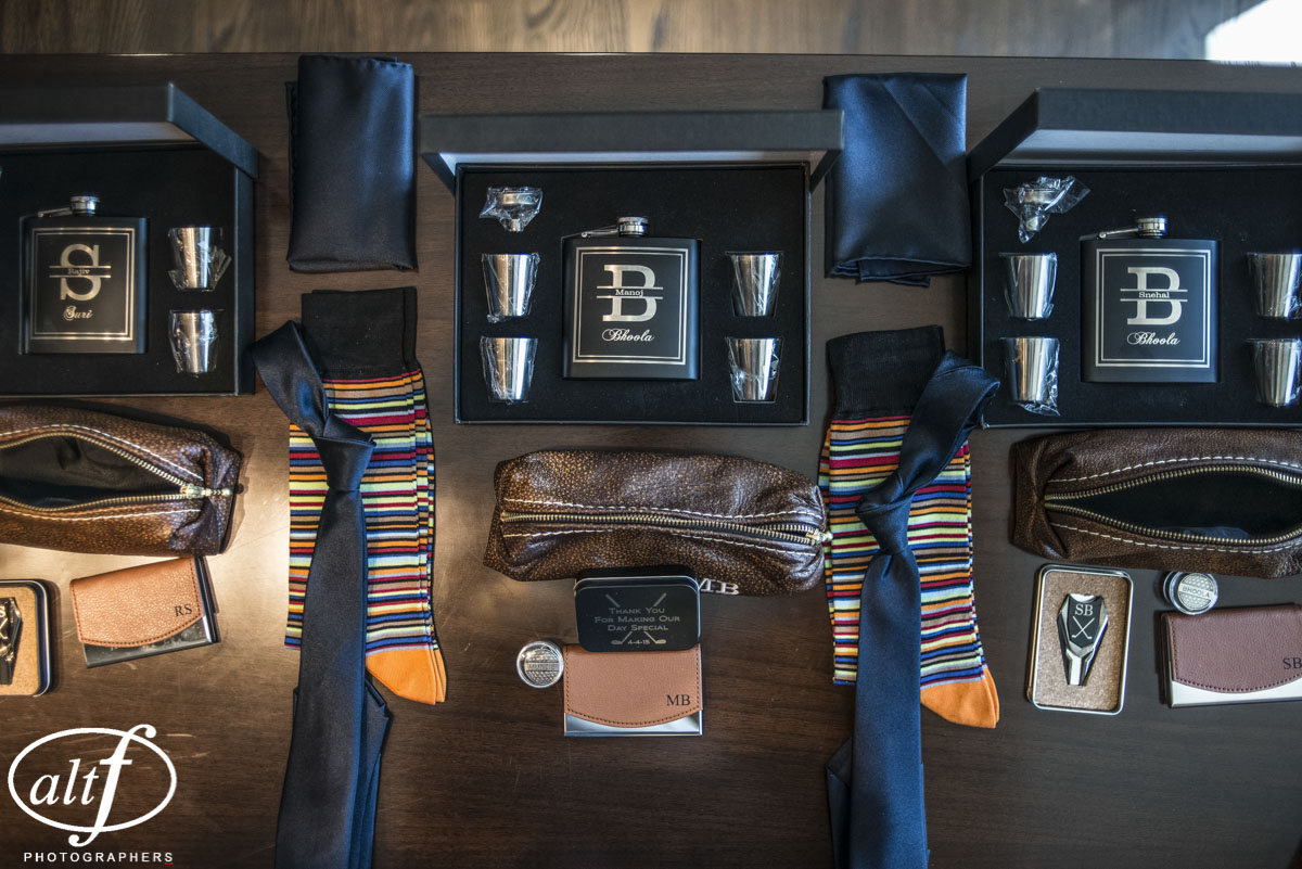 An over abundance of groomsmen gifts included engraved flasks, shot glasses, socks, ties, business card holders, golf tees, and more. Indian Wedding at the Mandarin Oriental. Las Vegas Wedding Planner Andrea Eppolito. Photo by Altf.