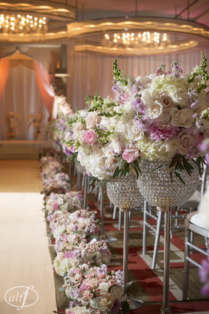 The aisle was lined with a gold aisle runner, and finished with crystal goblets filled with hydrangea, roses, and ranunculus.   Indian Wedding at the Mandarin Oriental. Las Vegas Wedding Planner Andrea Eppolito. Photo by Altf.