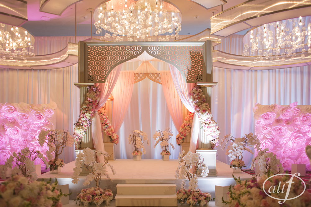 A luxury mandap made of gold laser cut wood, blush drapes, and roses in shades of cream and pink. The aisle was lined with a gold aisle rummer, and finished with crystal goblets filled with hydrangea, roses, and ranunculus. The sides of the mandap were decorated with white paper flower walls.   Indian Wedding at the Mandarin Oriental. Las Vegas Wedding Planner Andrea Eppolito. Photo by Altf.