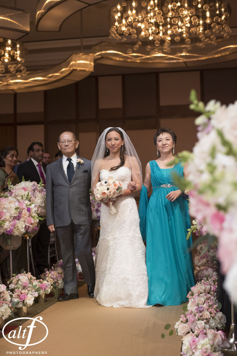 Bride being walked down the aisle by other of her parents. I  ndian Wedding at the Mandarin Oriental. Las Vegas Wedding Planner Andrea Eppolito. Photo by Altf.