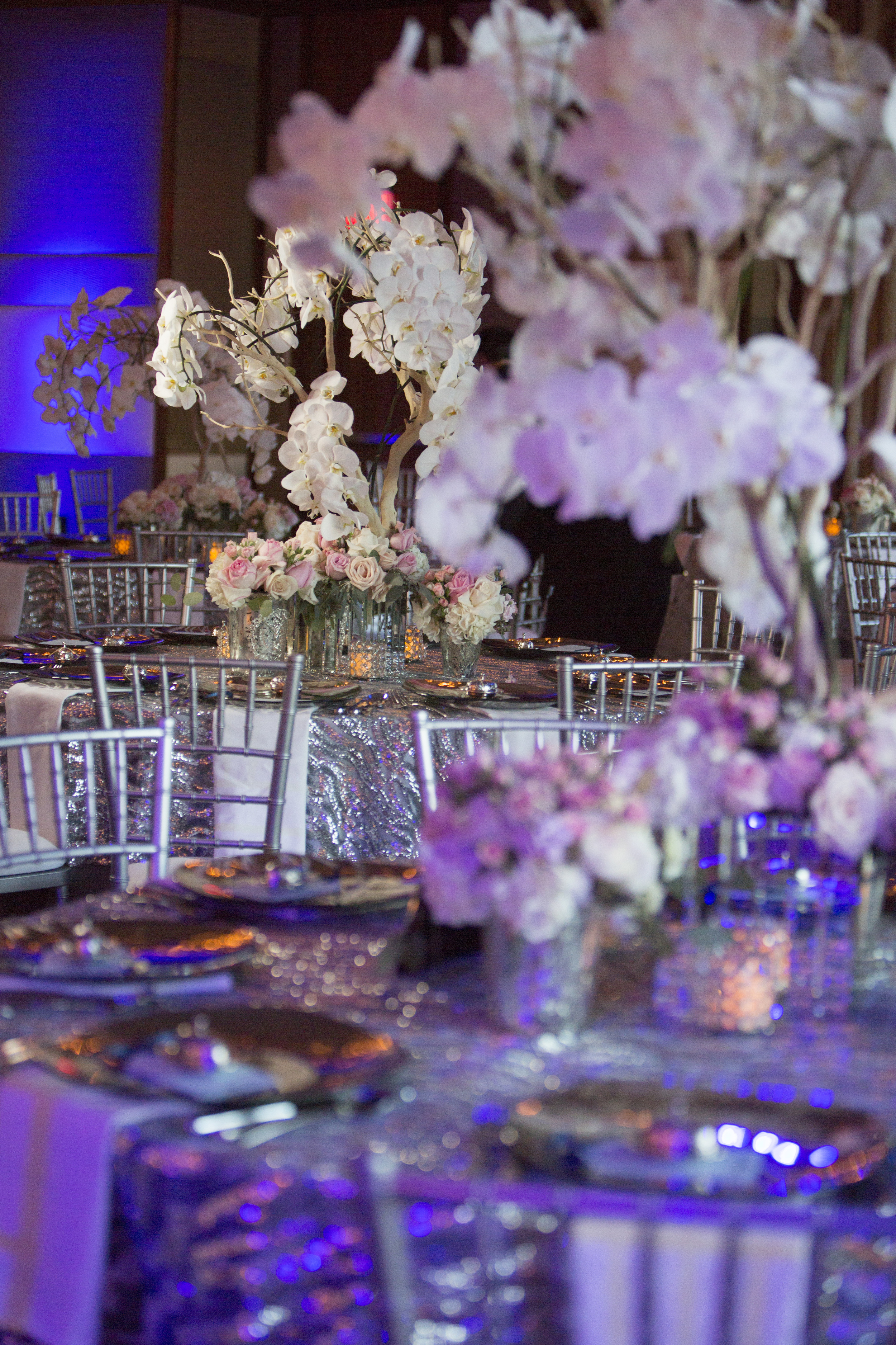 Luxury wedding reception featuring orchid trees, roses, silver table cloths, and chiavari chairs. Blue lighting.  Las Vegas Wedding Planner Andrea Eppolito. Photo by Altf. Florals  , Decor, and Entertainment by DBD Vegas.
