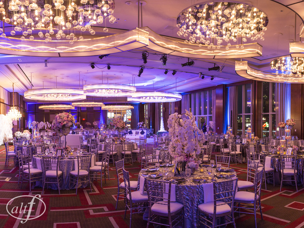 Luxury wedding reception featuring orchid trees, roses, silver table cloths, and chiavari chairs withblue and purplelighting in the ballroom at the Mandarin Oriental.   Las Vegas Wedding Planner Andrea Eppolito. Photo by Altf. Florals  , Decor, and Entertainment by DBD Vegas.