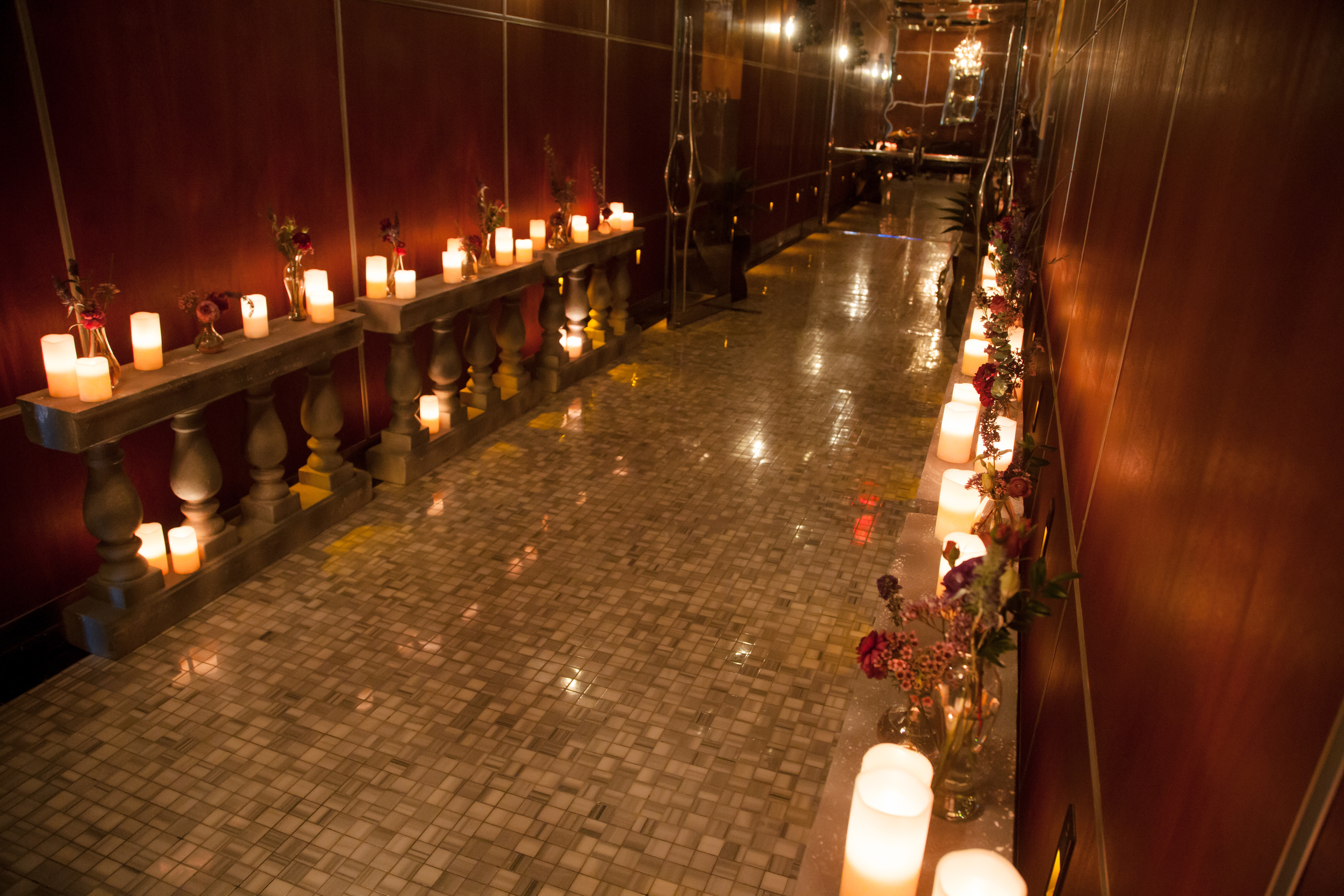 Candles and jewel toned florals line the entry of Bellagio. Las Vegas Wedding Planner and Eve  nt Designer Andrea Eppolito produces an Atonement themed party for  The Knot Rocks JCK 2016 for The Knot Pro. Photo by Adam Frazier.