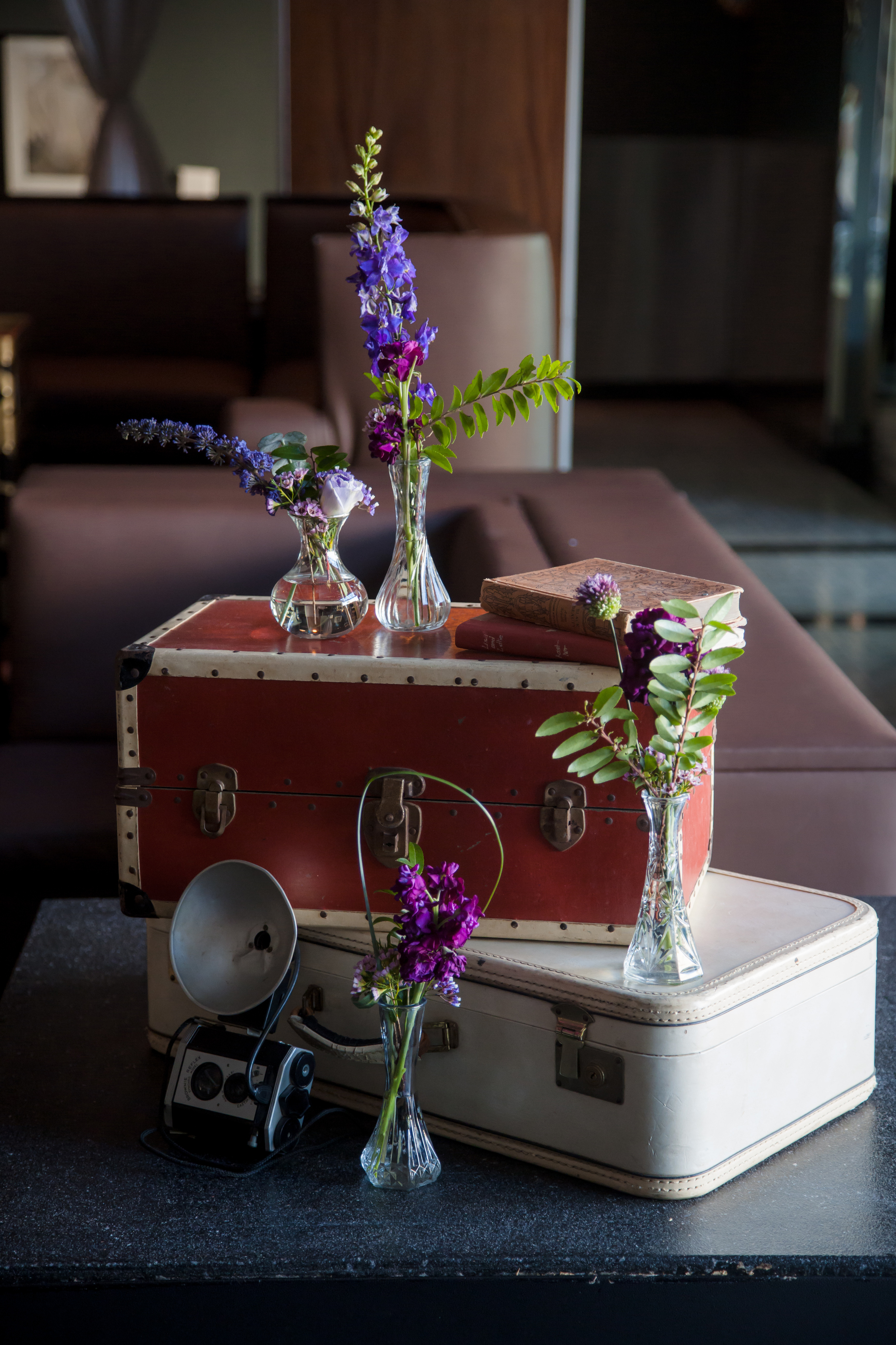 We drew inspiration from the movie Atonement and went with a vintage, 1920's style of decor with vintage suitcases and old cameras. Las Vegas Wedding Planner and Eve  nt Designer Andrea Eppolito produces an Atonement themed party for  The Knot Rocks JCK 2016 for The Knot Pro. Photo by Adam Frazier.