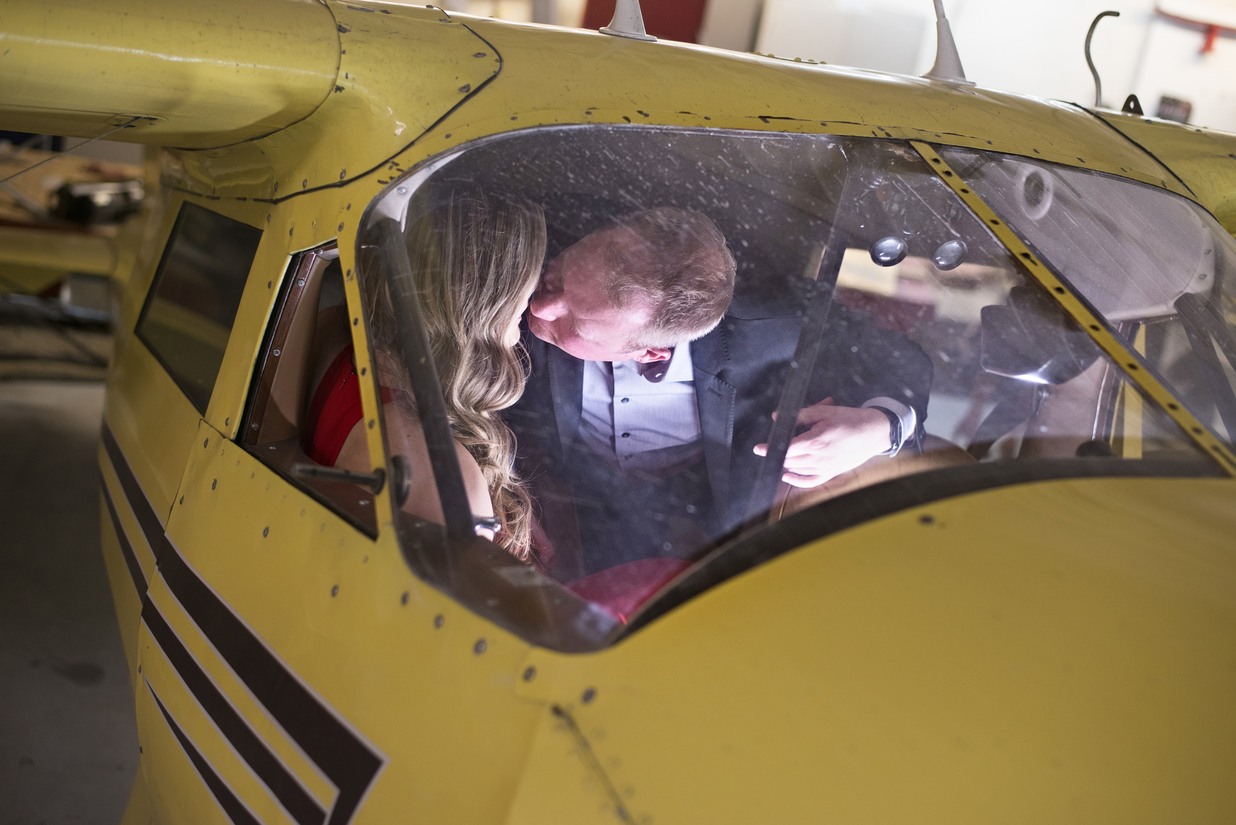 Destination Wedding Planner Andrea Eppolito | Engagement Photos in an Airplane Hanger | Images by   AltF Photography   | Kissing in a plane