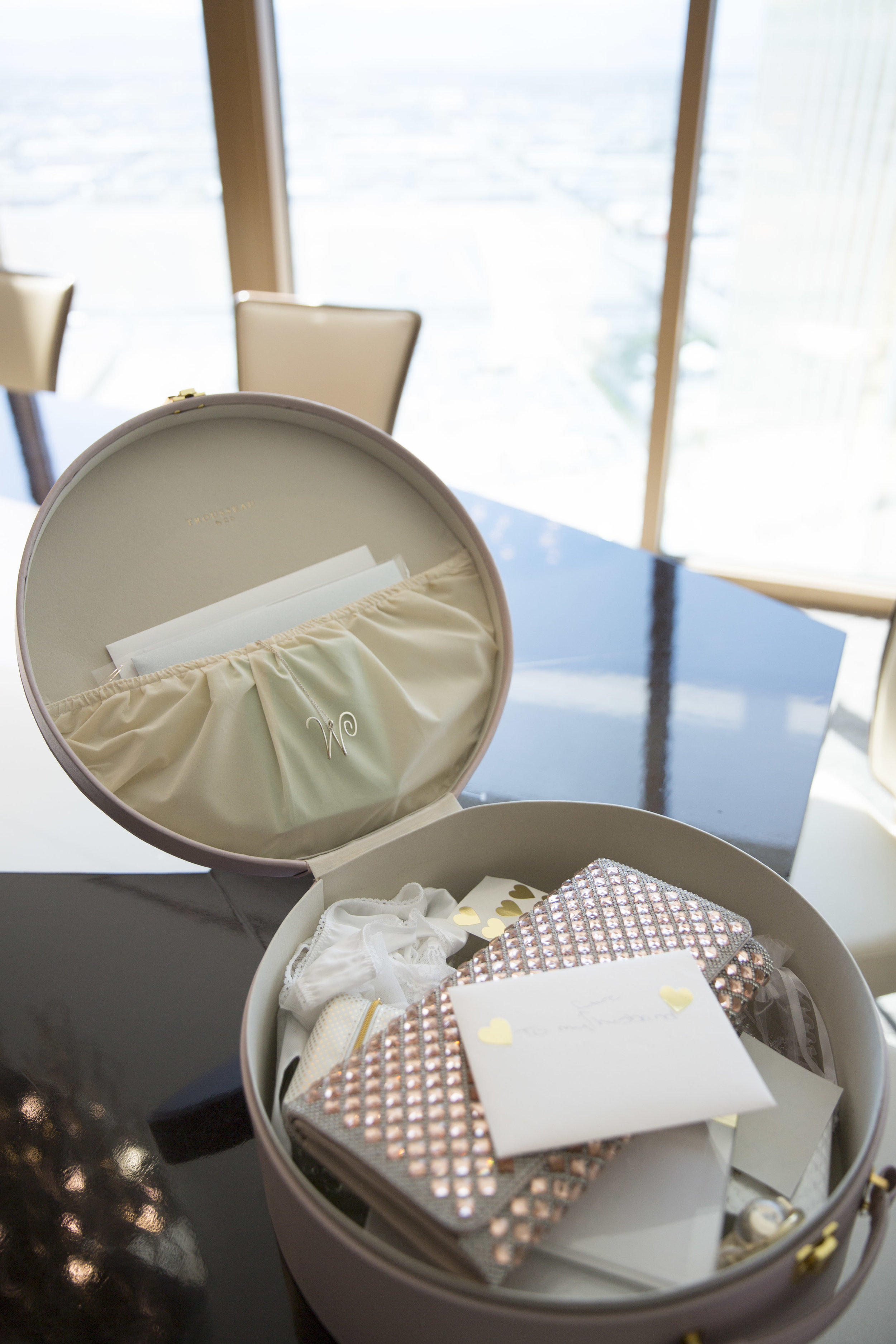 Trousseau Case filled with bridal clutch by Aldo, garters, and cards. Las Vegas Wedding Planner Andrea Eppolito | Florals & Decor by DBD Vegas | Image by AltF Photography.