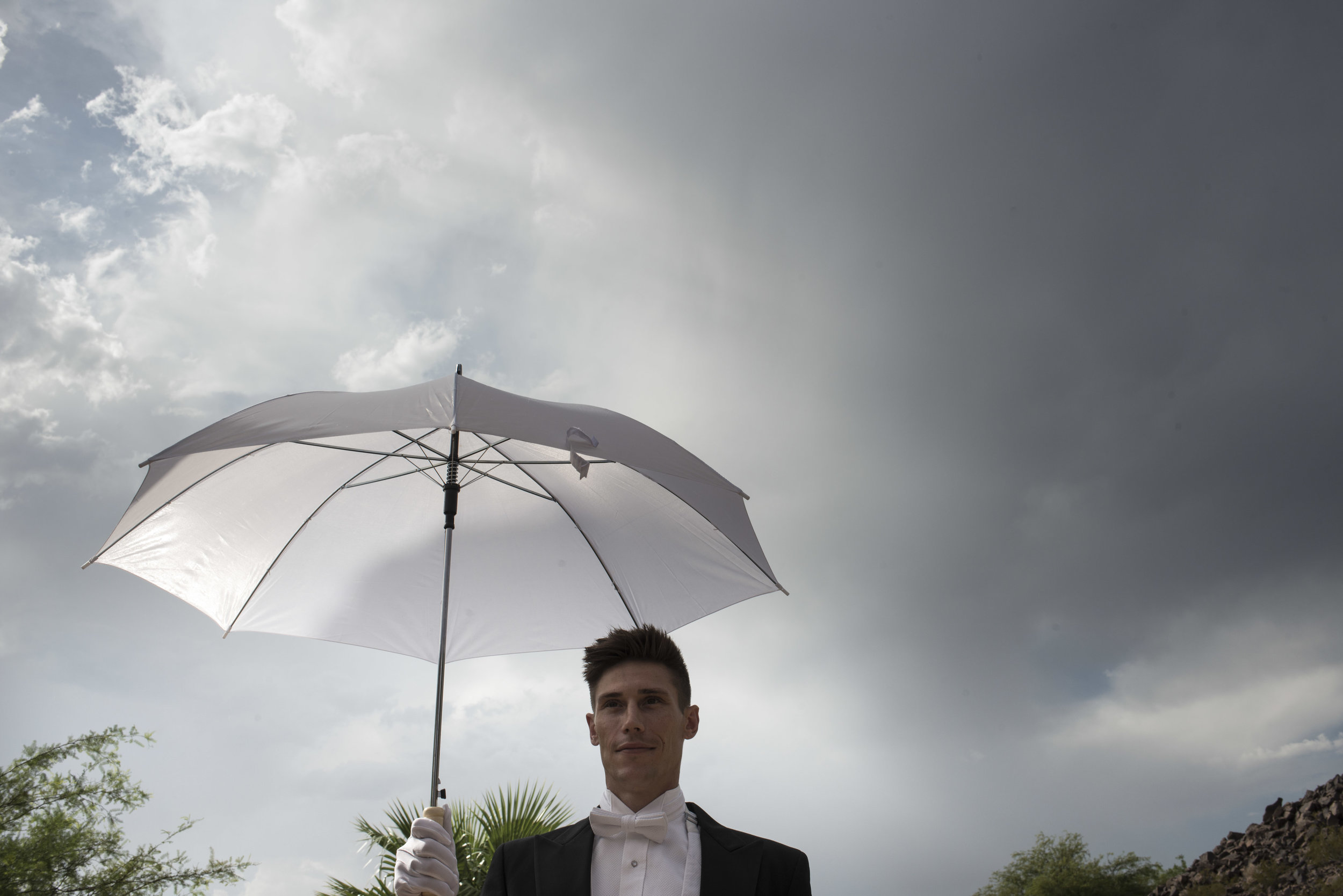 Butlers with umbrellas to shield guests from the sun as they arrive to the wedding. Luxury Las Vegas Wedding Planner Andrea Eppolito. Image by AltF Photography.