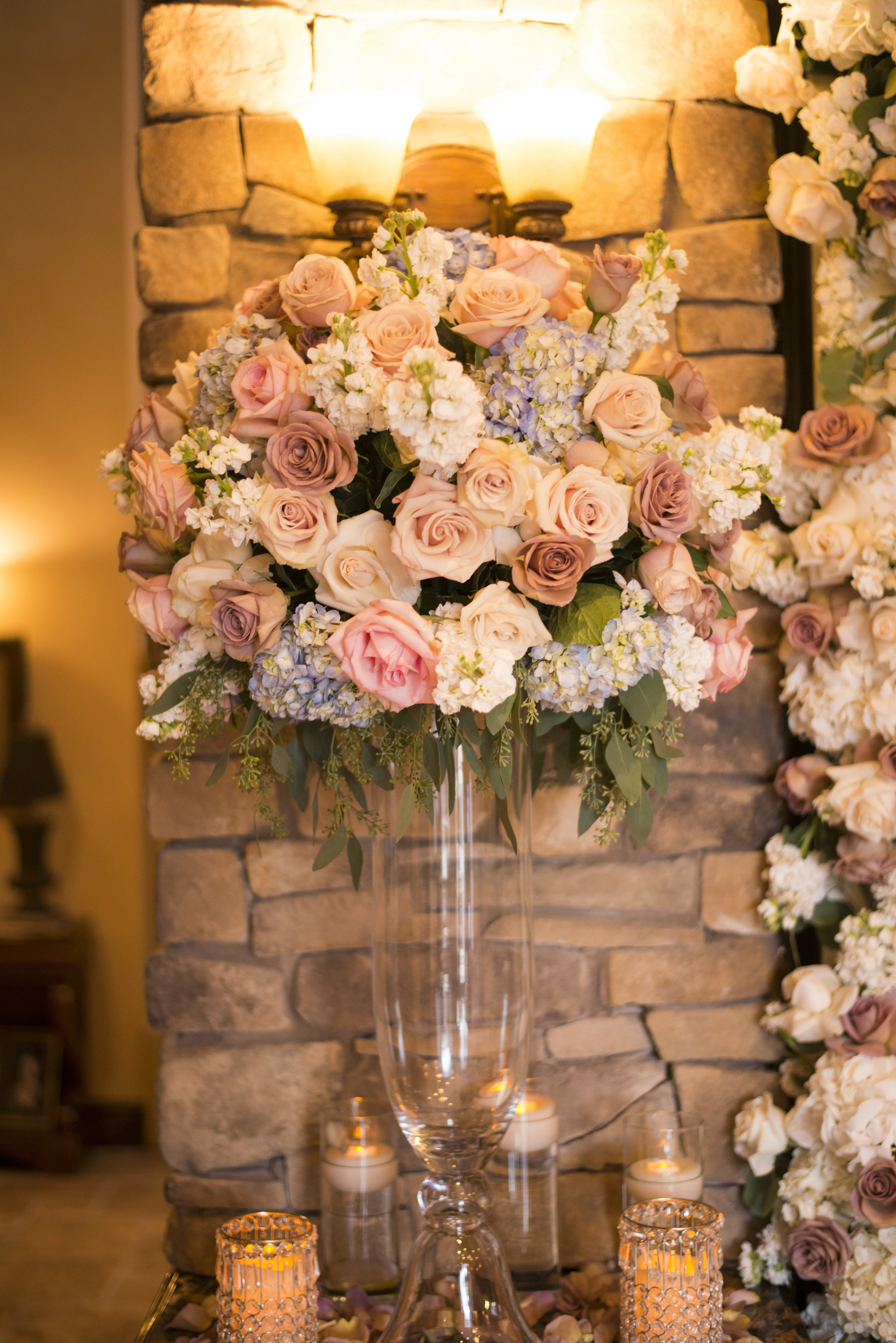 Big pink floral arrangement surrounded by candles at private estate wedding in Las Vegas. Luxury Las Vegas Wedding Planner Andrea Eppolito. Image by AltF Photography.