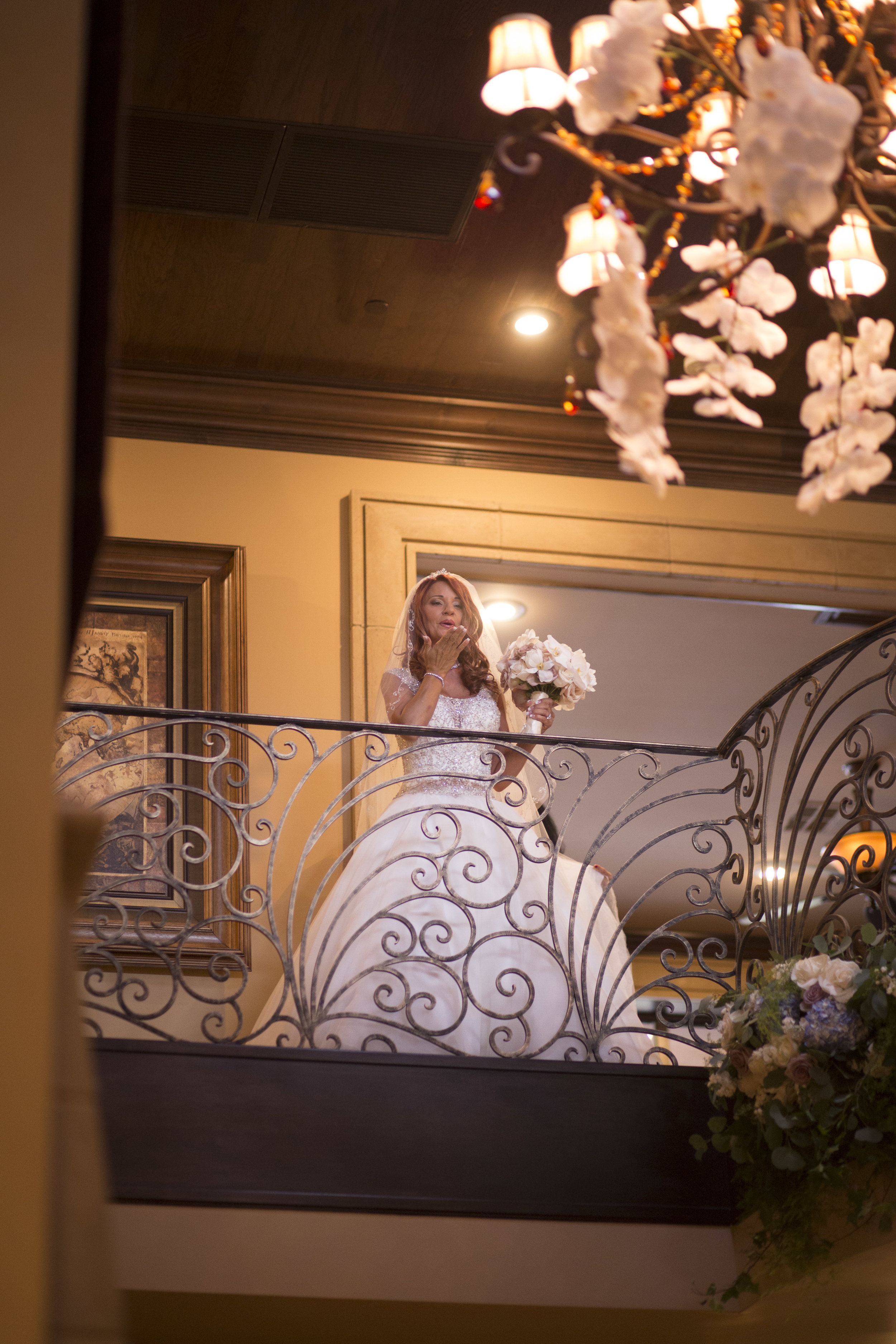 Bride blows a kiss to the groom from balcony. Luxury Las Vegas Wedding Planner Andrea Eppolito. Image by AltF Photography.