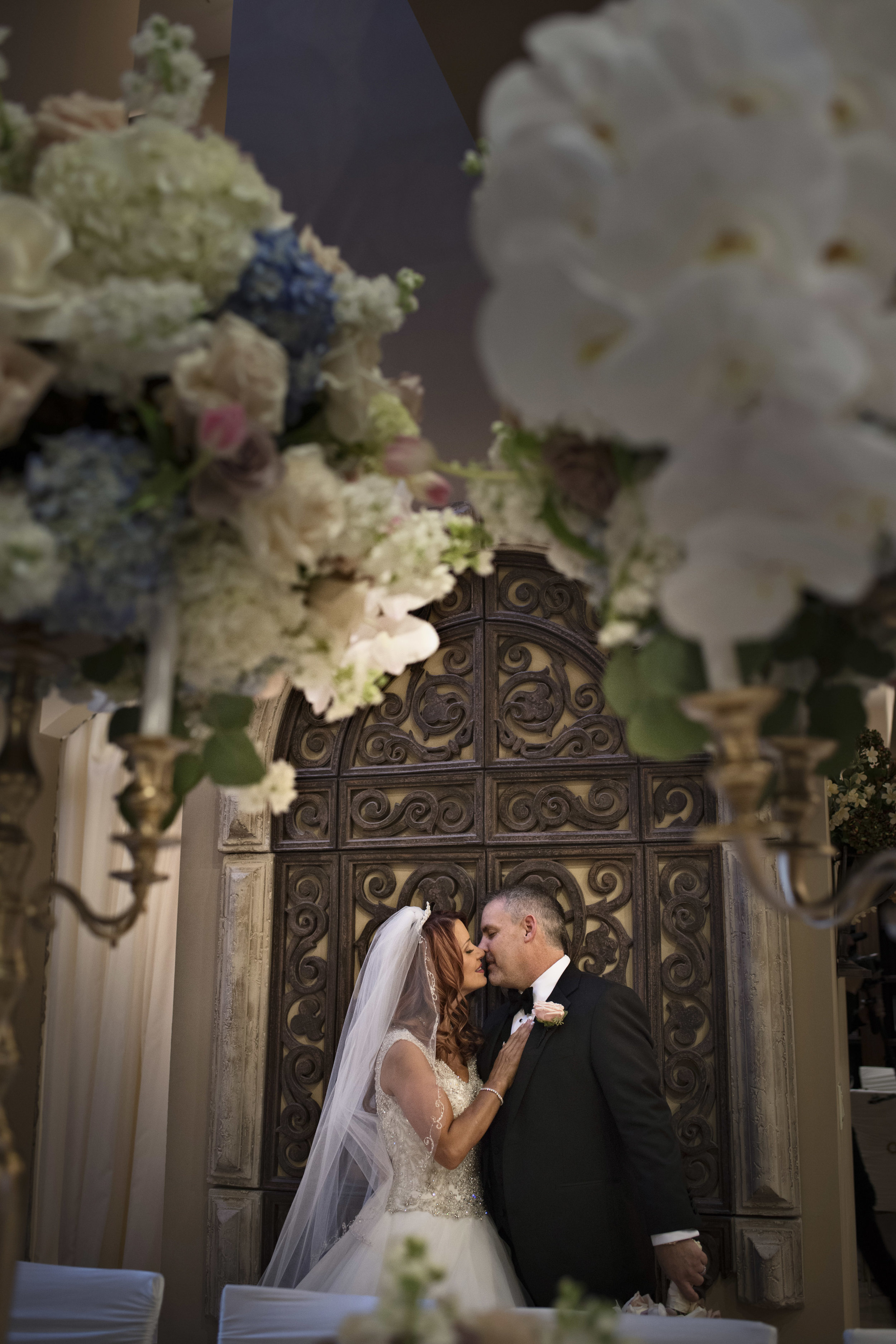 Bride and groom portrait in front of a gate. Luxury Las Vegas Wedding Planner Andrea Eppolito. Image by AltF Photography.