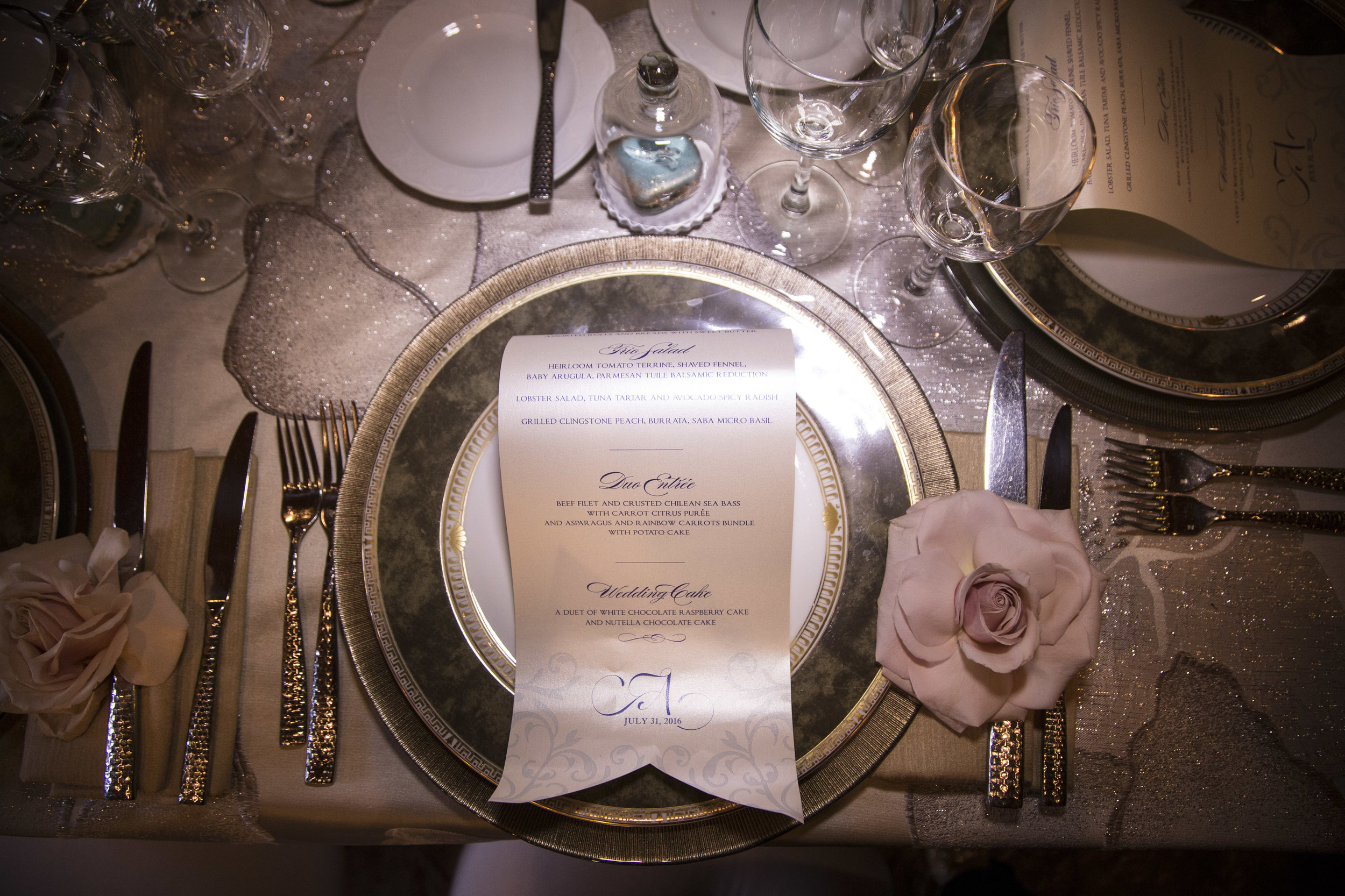 Luxury Place Setting for Castle wedding featuring a scrolled menu, embroidered linens, rose accent, and individual glass slipper favor. Luxury Las Vegas Wedding Planner Andrea Eppolito. Image by AltF Photography.