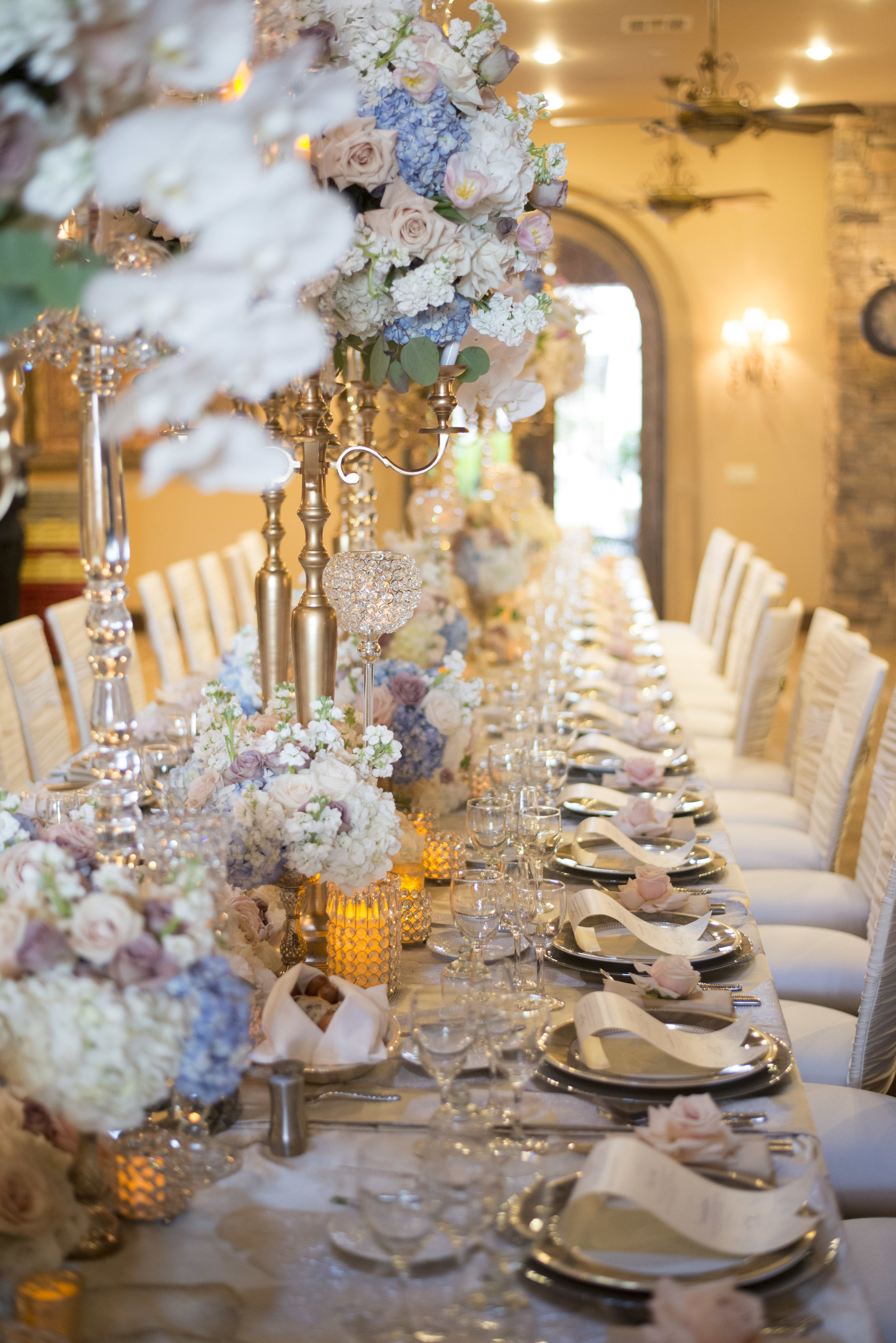 Long banquet table wit tall centerpieces and elaborate place settings in blue and pink. Luxury Las Vegas Wedding Planner Andrea Eppolito. Image by AltF Photography.