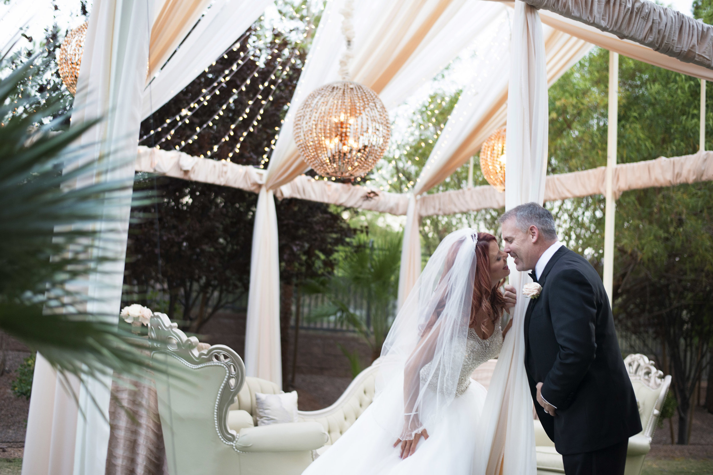 Bride and groom kiss in a custom open air tent with light orbs and twinkle lights by LED Unplugged and DBD Vegas. Luxury Las Vegas Wedding Planner Andrea Eppolito. Image by AltF Photography.