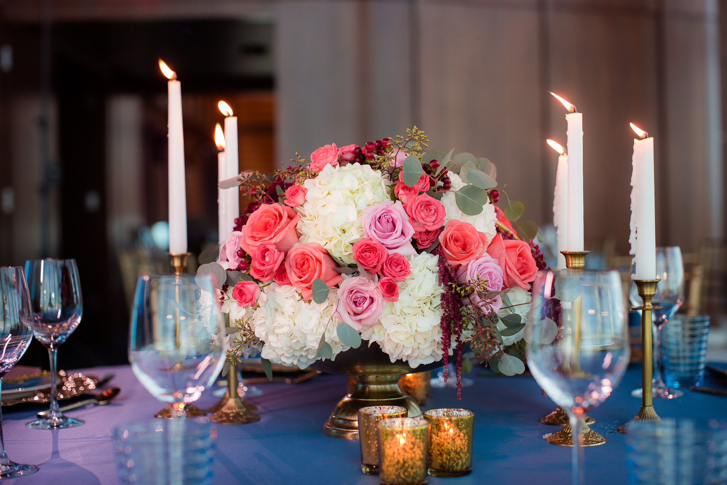 Live candles at wedding reception with blue linen and rich centerpieces.     Styled Wedding Shoot inspired by French Blue.    Las Vegas Wedding Planner  Andrea Eppolito .  Photography by   Rebecca Marie  .  Floral and Decor by   By Dzign  .  Beauty by   Amelia C & Co  .  Shot at Rivea at The Delano.
