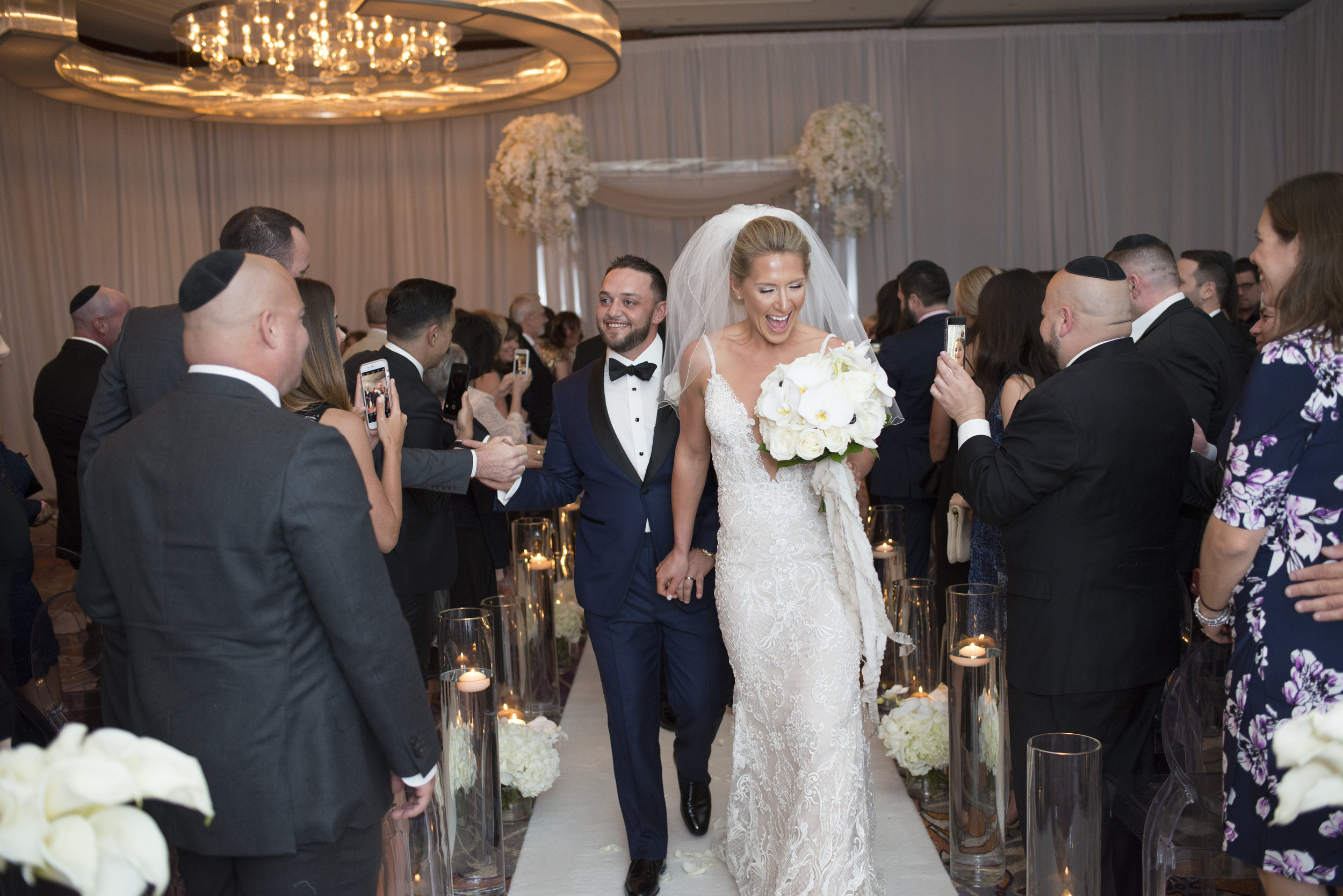 Newlyweds walk down the aisle after being married in a Jewish destination wedding.WEDDING PLANNING & EVENT DESIGN • Andrea Eppolito Events ,PHOTOGRAPHY • AltF Photography ,FLORAL AND DECOR DESIGN & PRODUCTION • Destinations by Design , CATERING • Mandarin Oriental Las Vegas , COCKTAILS •  The Grand Bevy , WEDDING GOWN •  Galia Lahav ,SHOES •  Jimmy Choo