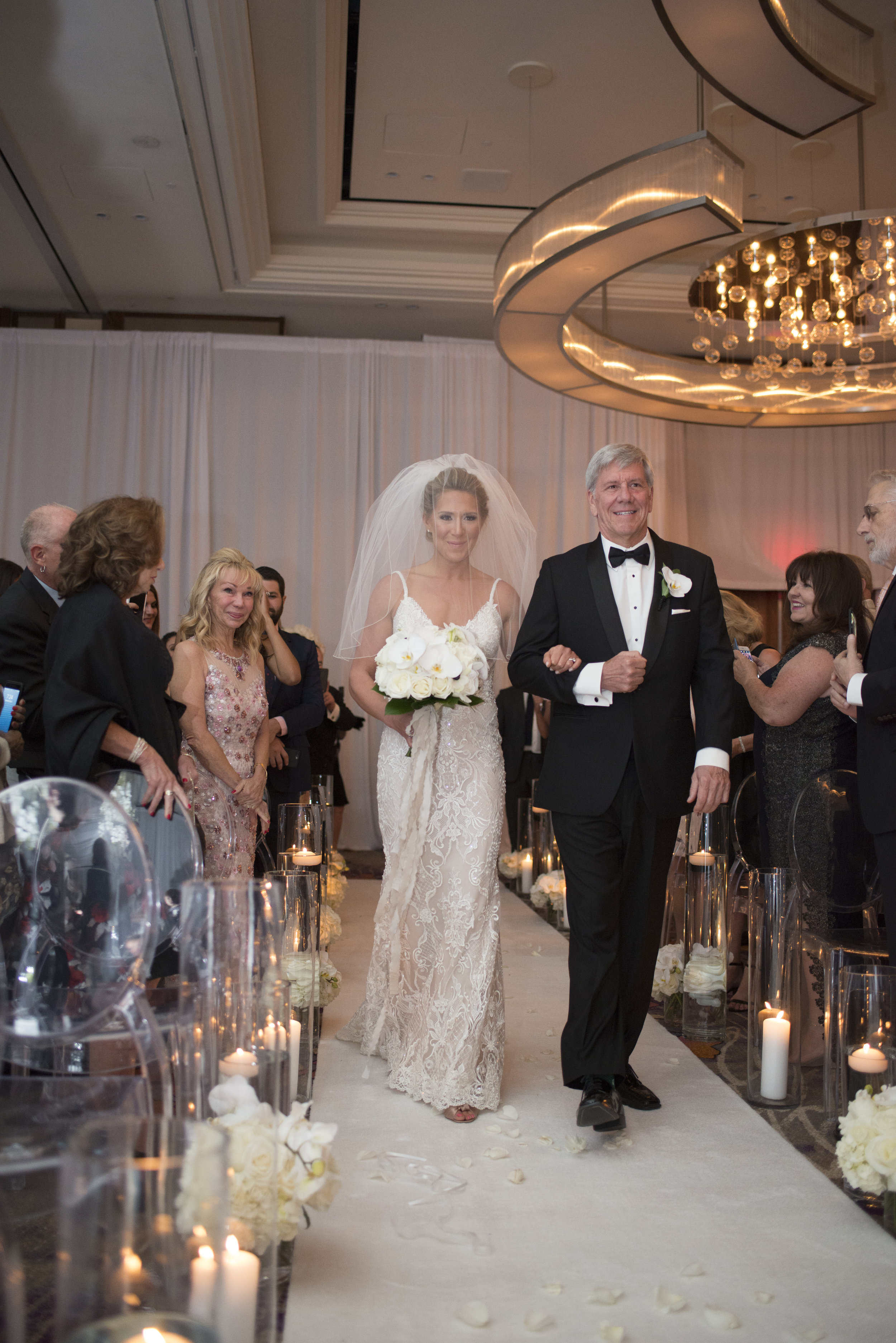 Jewish Wedding Ceremony. Bride being escorted down the aisle by her father. WEDDING PLANNING & EVENT DESIGN • Andrea Eppolito Events ,PHOTOGRAPHY • AltF Photography ,FLORAL AND DECOR DESIGN & PRODUCTION • Destinations by Design , CATERING • Mandarin Oriental Las Vegas , COCKTAILS •  The Grand Bevy , WEDDING GOWN •  Galia Lahav ,SHOES •  Jimmy Choo