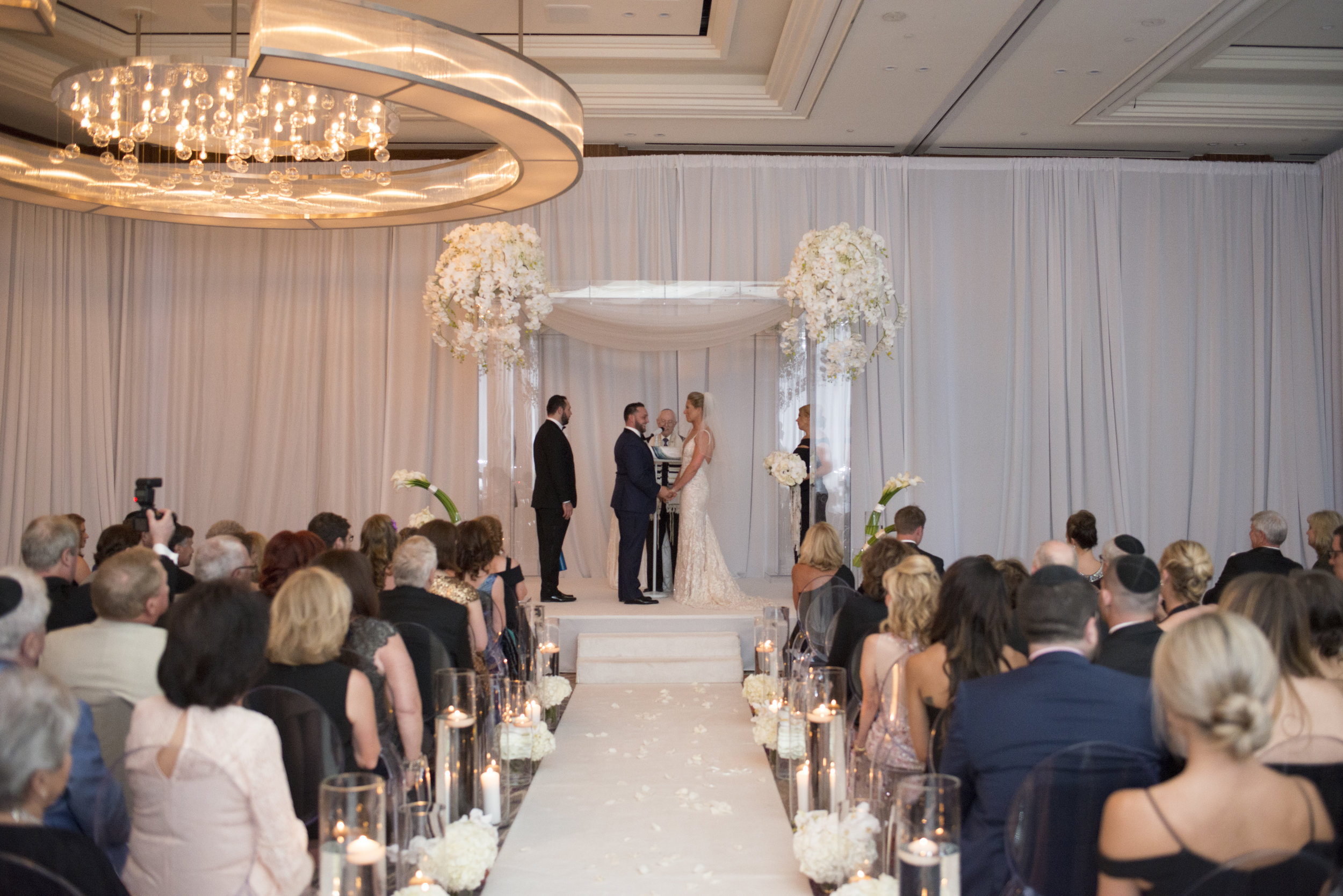 Luxe Jewish wedding ceremony with acrylic chuppah and orchids.WEDDING PLANNING & EVENT DESIGN • Andrea Eppolito Events ,PHOTOGRAPHY • AltF Photography ,FLORAL AND DECOR DESIGN & PRODUCTION • Destinations by Design , CATERING • Mandarin Oriental Las Vegas , COCKTAILS •  The Grand Bevy , WEDDING GOWN •  Galia Lahav ,SHOES •  Jimmy Choo