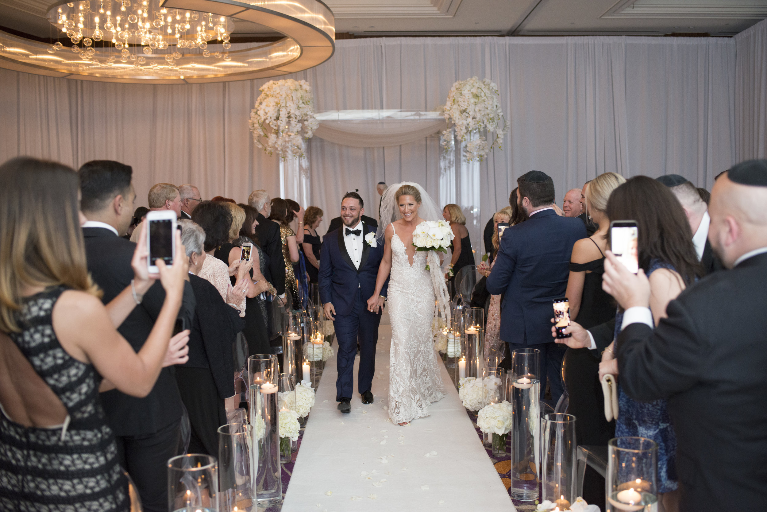 Mr. and Mrs. Wedding recessional in white on white wedding. WEDDING PLANNING & EVENT DESIGN • Andrea Eppolito Events ,PHOTOGRAPHY • AltF Photography ,FLORAL AND DECOR DESIGN & PRODUCTION • Destinations by Design , CATERING • Mandarin Oriental Las Vegas , COCKTAILS •  The Grand Bevy , WEDDING GOWN •  Galia Lahav ,SHOES •  Jimmy Choo
