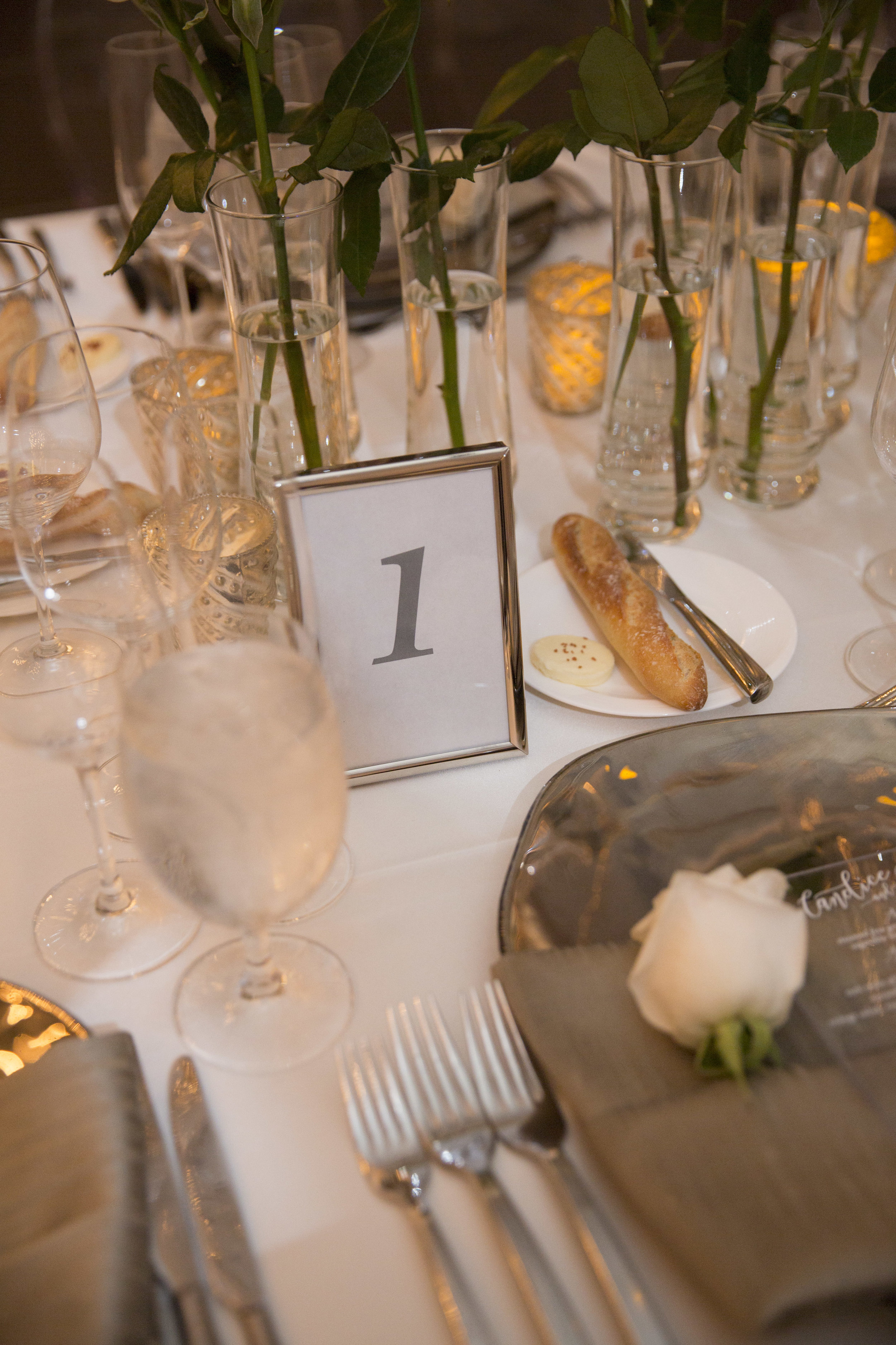 Clean silver table frames hold grey printed table numbers. White roses at each place setting. WEDDING PLANNING & EVENT DESIGN • Andrea Eppolito Events ,PHOTOGRAPHY • AltF Photography ,FLORAL AND DECOR DESIGN & PRODUCTION • Destinations by Design , CATERING • Mandarin Oriental Las Vegas , COCKTAILS •  The Grand Bevy , WEDDING GOWN •  Galia Lahav ,SHOES •  Jimmy Choo , ACRYLIC MENUS & SEATING CHART•  She Paperie