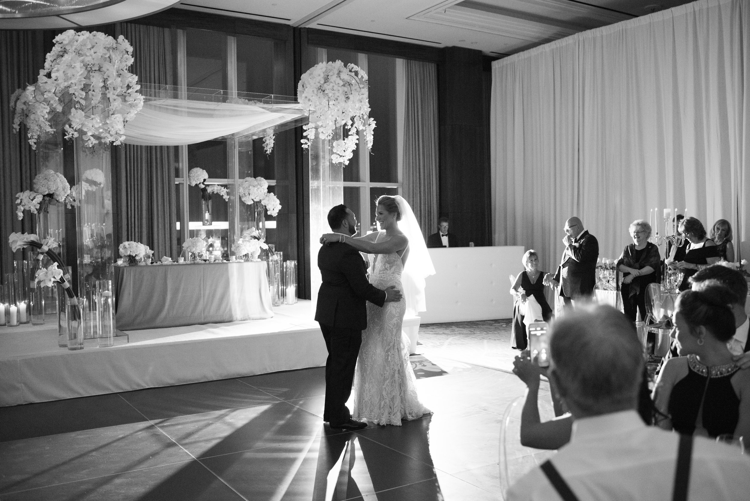 Bride and groom share their first dance on the black dance floor with white applique. WEDDING PLANNING & EVENT DESIGN • Andrea Eppolito Events ,PHOTOGRAPHY • AltF Photography ,FLORAL AND DECOR DESIGN & PRODUCTION • Destinations by Design , CATERING • Mandarin Oriental Las Vegas , COCKTAILS •  The Grand Bevy , WEDDING GOWN •  Galia Lahav ,SHOES •  Jimmy Choo , ACRYLIC MENUS & SEATING CHART•  She Paperie
