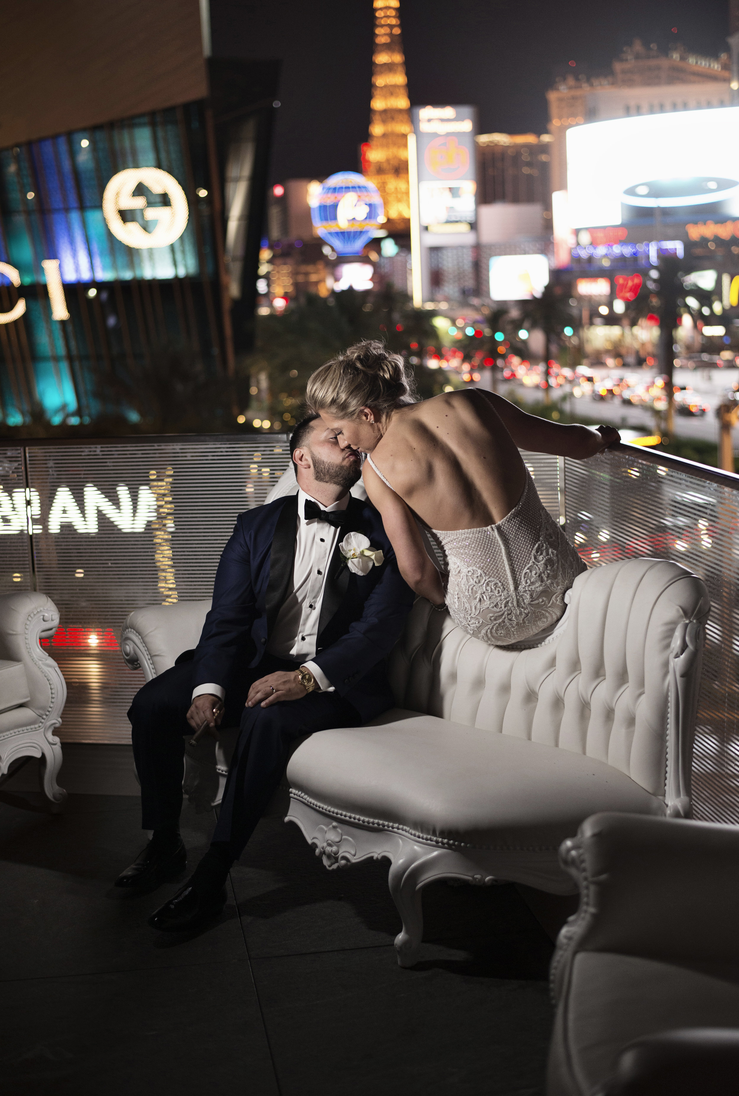 Bride & groom kiss on the balcony of The Mandarin Oriental.WEDDING PLANNING & EVENT DESIGN • Andrea Eppolito Events ,PHOTOGRAPHY • AltF Photography ,FLORAL AND DECOR DESIGN & PRODUCTION • Destinations by Design , CATERING • Mandarin Oriental Las Vegas , COCKTAILS •  The Grand Bevy , WEDDING GOWN •  Galia Lahav ,SHOES •  Jimmy Choo , ACRYLIC MENUS & SEATING CHART•  She Paperie