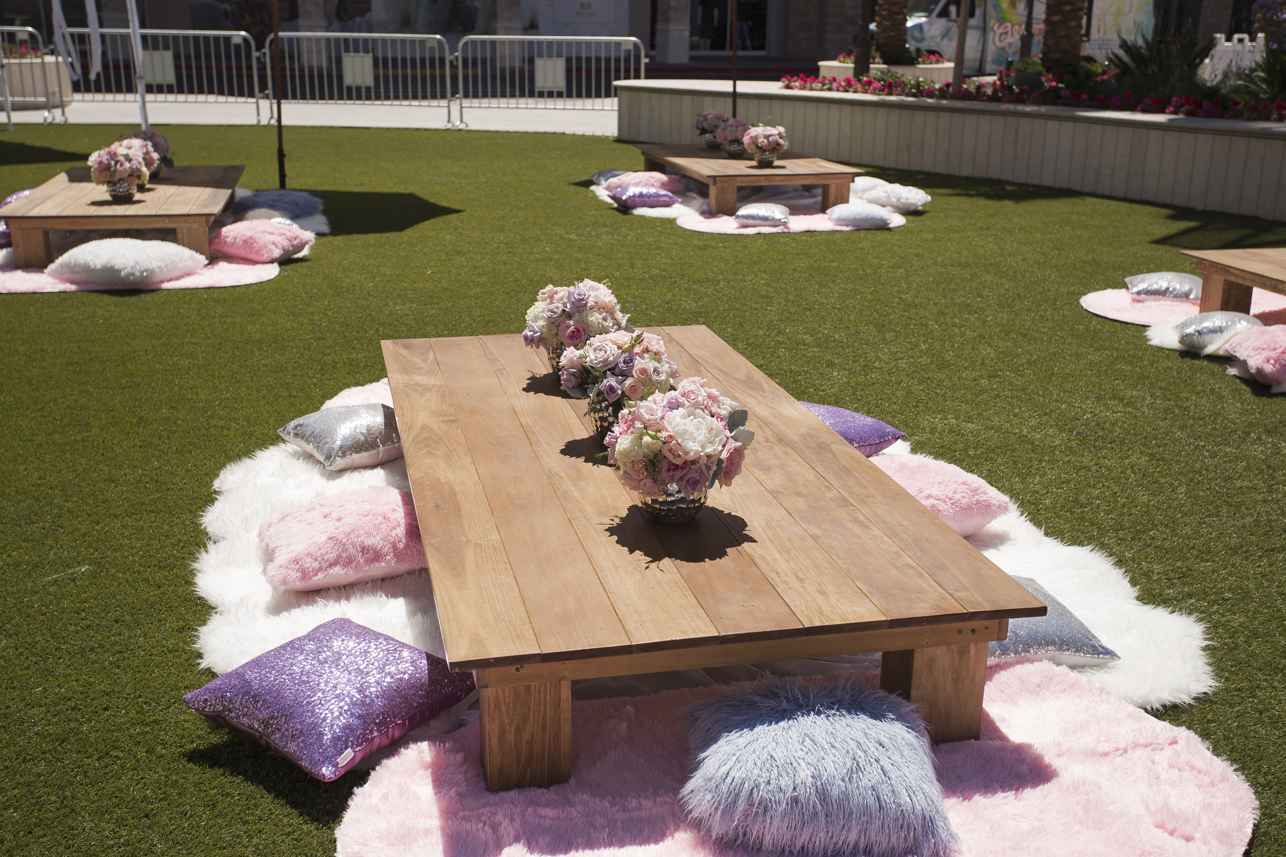 Wooden picnic tables with white and ivory roses.  Sequence pillows and fur rugs completed the looks.  Celebrity Event Planner Andrea Eppolito.  Floral and Rentals by Destinations by Design. Photo by Triple Vision Studios.