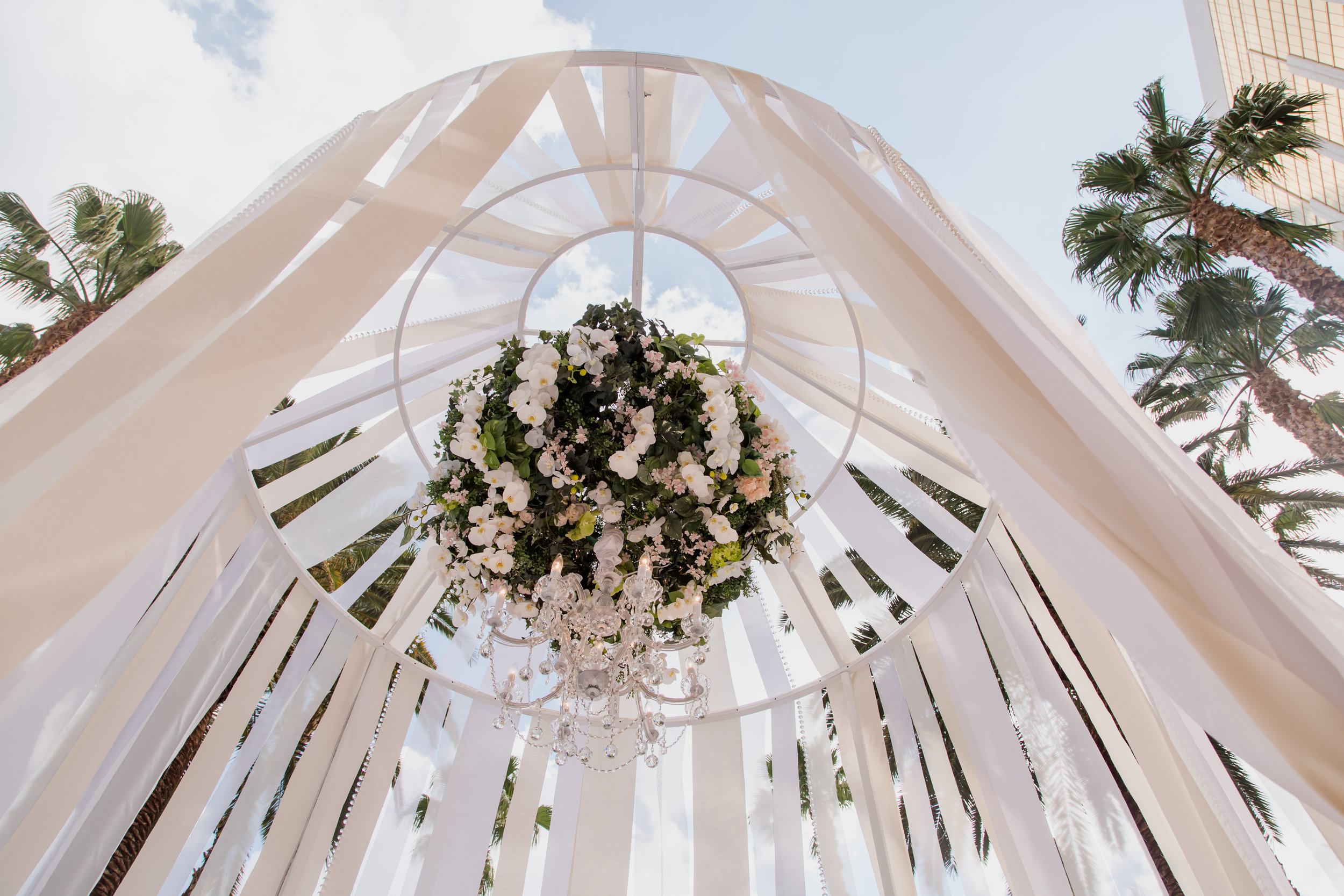 Birdcage and ribbon ceremony stage with floral chandelier. Destination Wedding Planner  Andrea Eppolito ·Photos by  Adam Frazier Photography ·Floral and Decor by  Destinations by Design · Lighting by  LED Unplugged ·Venue · Invitations  Ceci New York  · Menus by  Alligator Soup