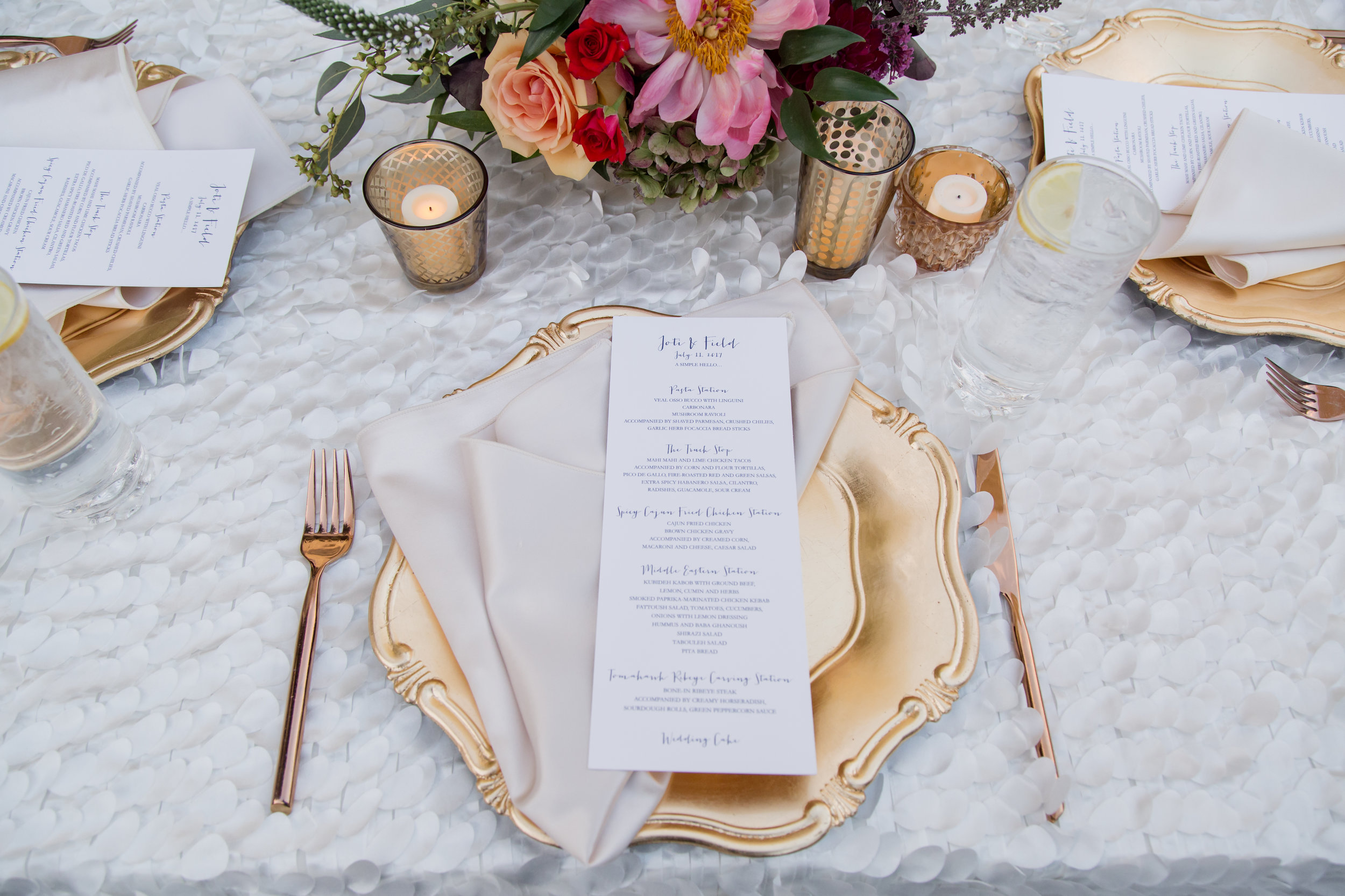 Gold place settings on white flutter linens with long menus and jewel toned florals.Destination Wedding Planner  Andrea Eppolito ·Photos by  Adam Frazier Photography ·Floral and Decor by  Destinations by Design · Lighting by  LED Unplugged ·Venue · Invitations  Ceci New York  · Menus by  Alligator Soup