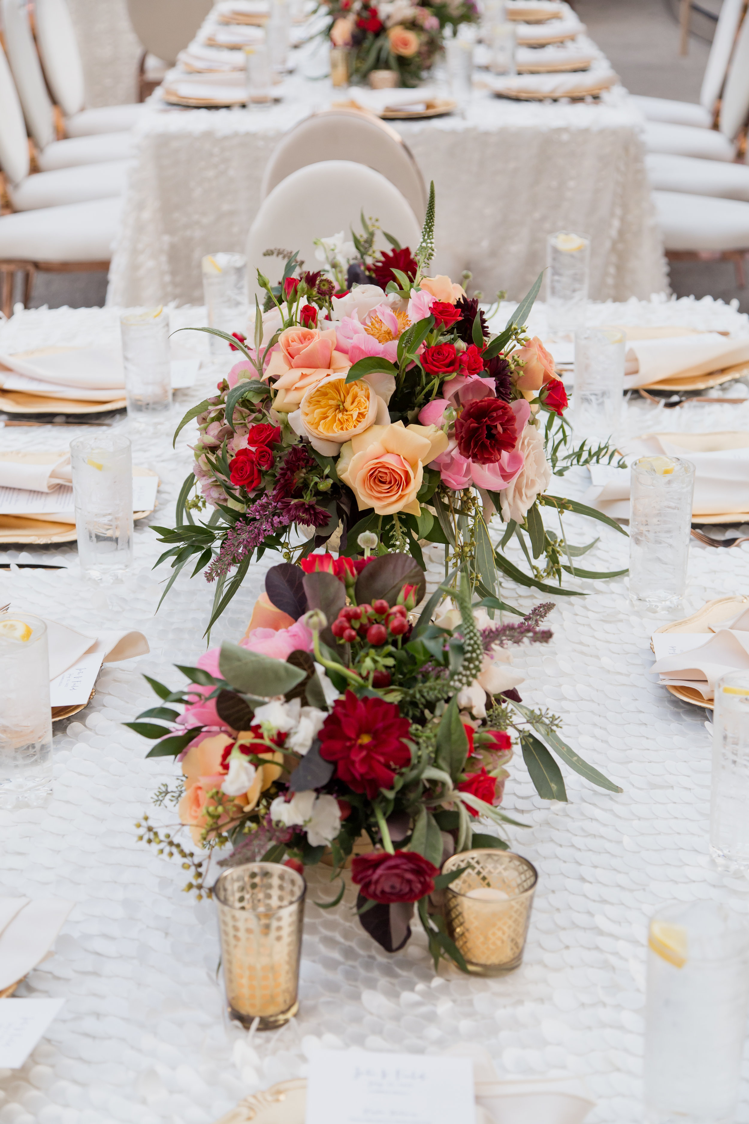 Jewel toned wedding centerpieces with gold votives on white flutter linen.Destination Wedding Planner  Andrea Eppolito ·Photos by  Adam Frazier Photography ·Floral and Decor by  Destinations by Design · Lighting by  LED Unplugged ·Venue · Invitations  Ceci New York  · Menus by  Alligator Soup