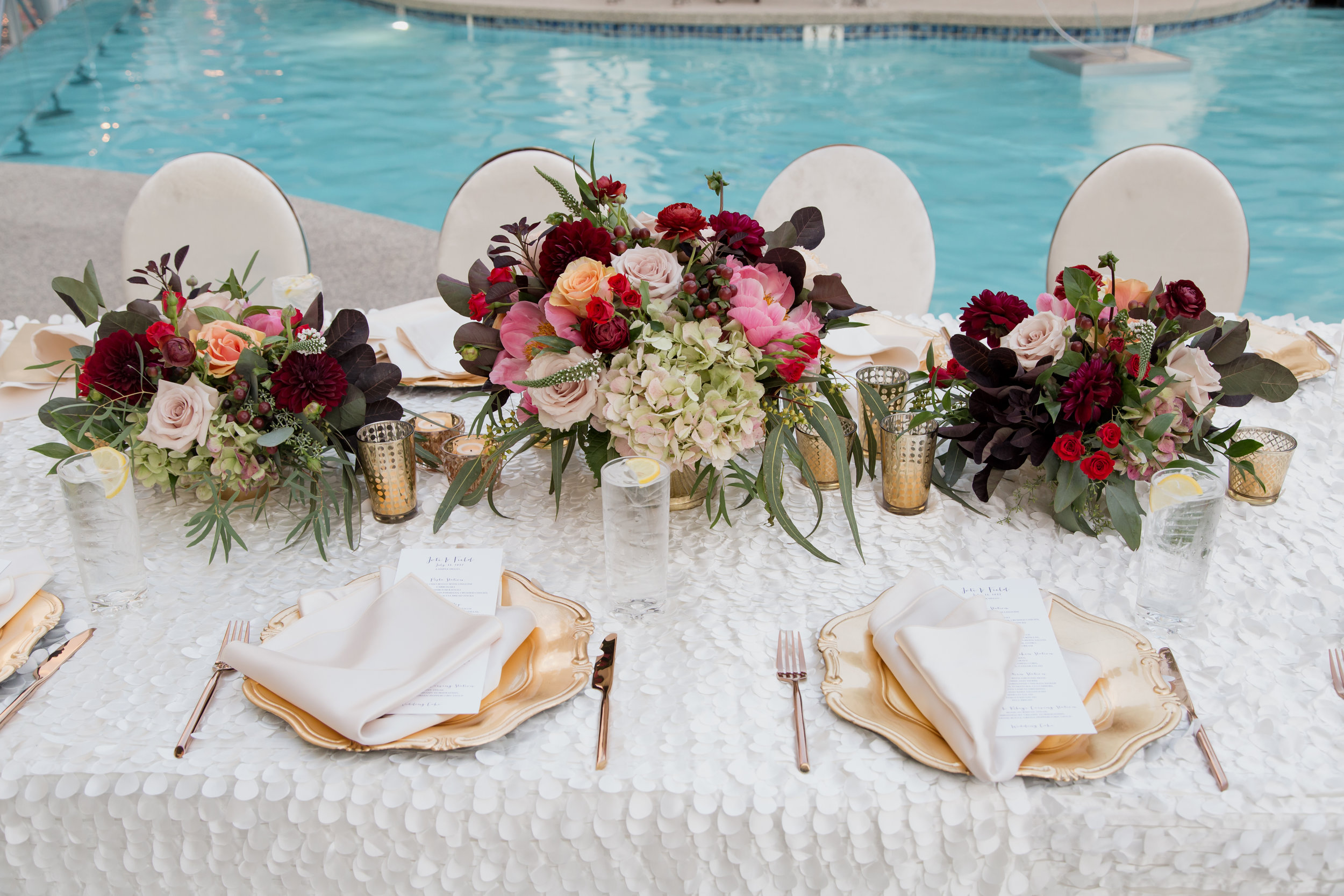 Jewel toned centerpieces with gold chargers at poolside wedding.Destination Wedding Planner  Andrea Eppolito ·Photos by  Adam Frazier Photography ·Floral and Decor by  Destinations by Design · Lighting by  LED Unplugged ·Venue · Invitations  Ceci New York  · Menus by  Alligator Soup