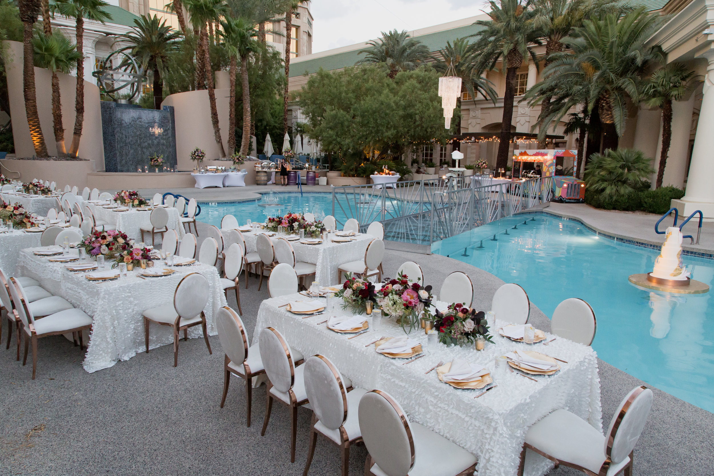 Poolside wedding in Las Vegas with chandeliers and floating wedding cake.Destination Wedding Planner  Andrea Eppolito ·Photos by  Adam Frazier Photography ·Floral and Decor by  Destinations by Design · Lighting by  LED Unplugged ·Venue · Invitations  Ceci New York  · Menus by  Alligator Soup