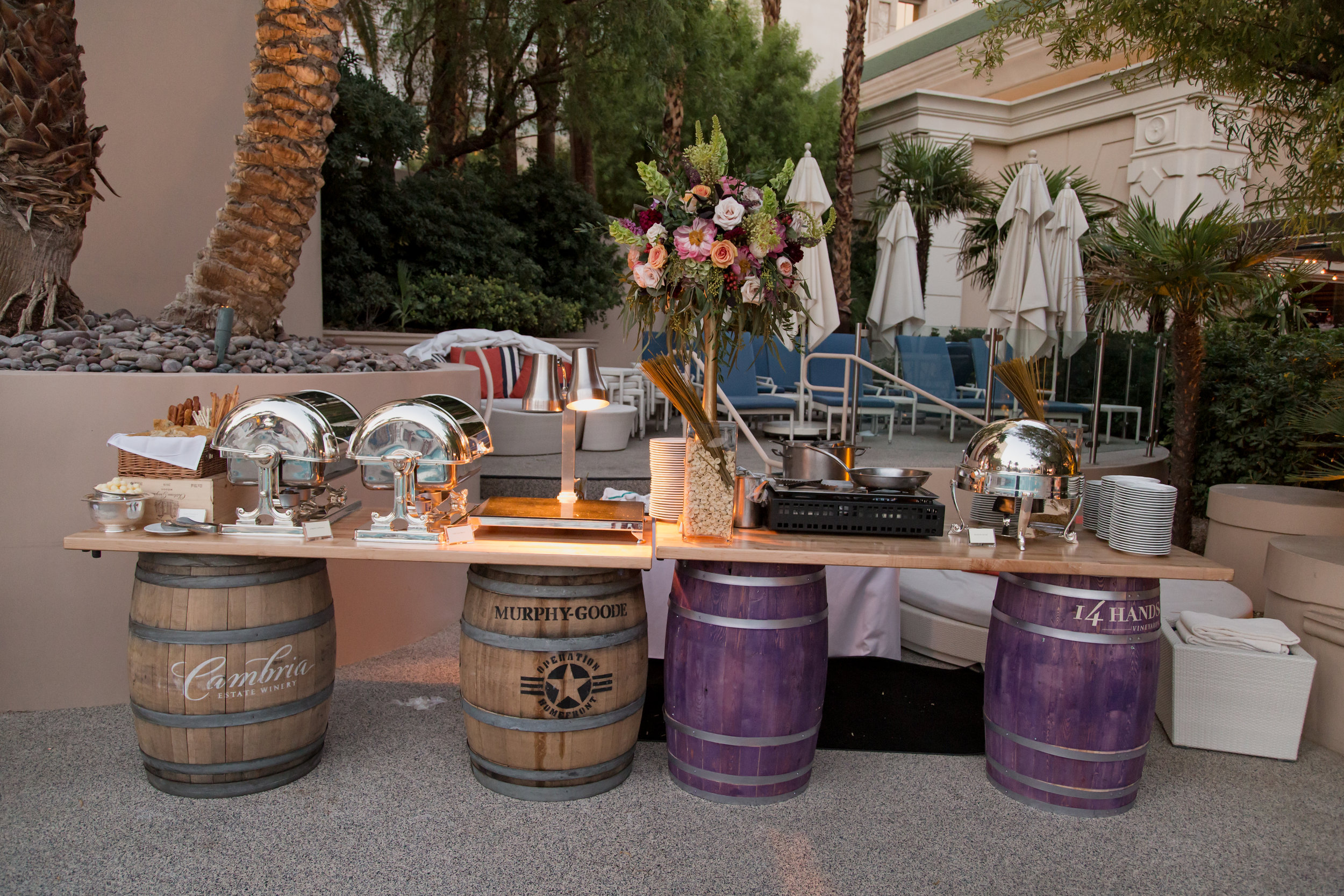 Food stations on wine barrels for wedding at poolside. Destination Wedding Planner  Andrea Eppolito ·Photos by  Adam Frazier Photography ·Floral and Decor by  Destinations by Design · Lighting by  LED Unplugged ·Venue · Invitations  Ceci New York  · Menus by  Alligator Soup